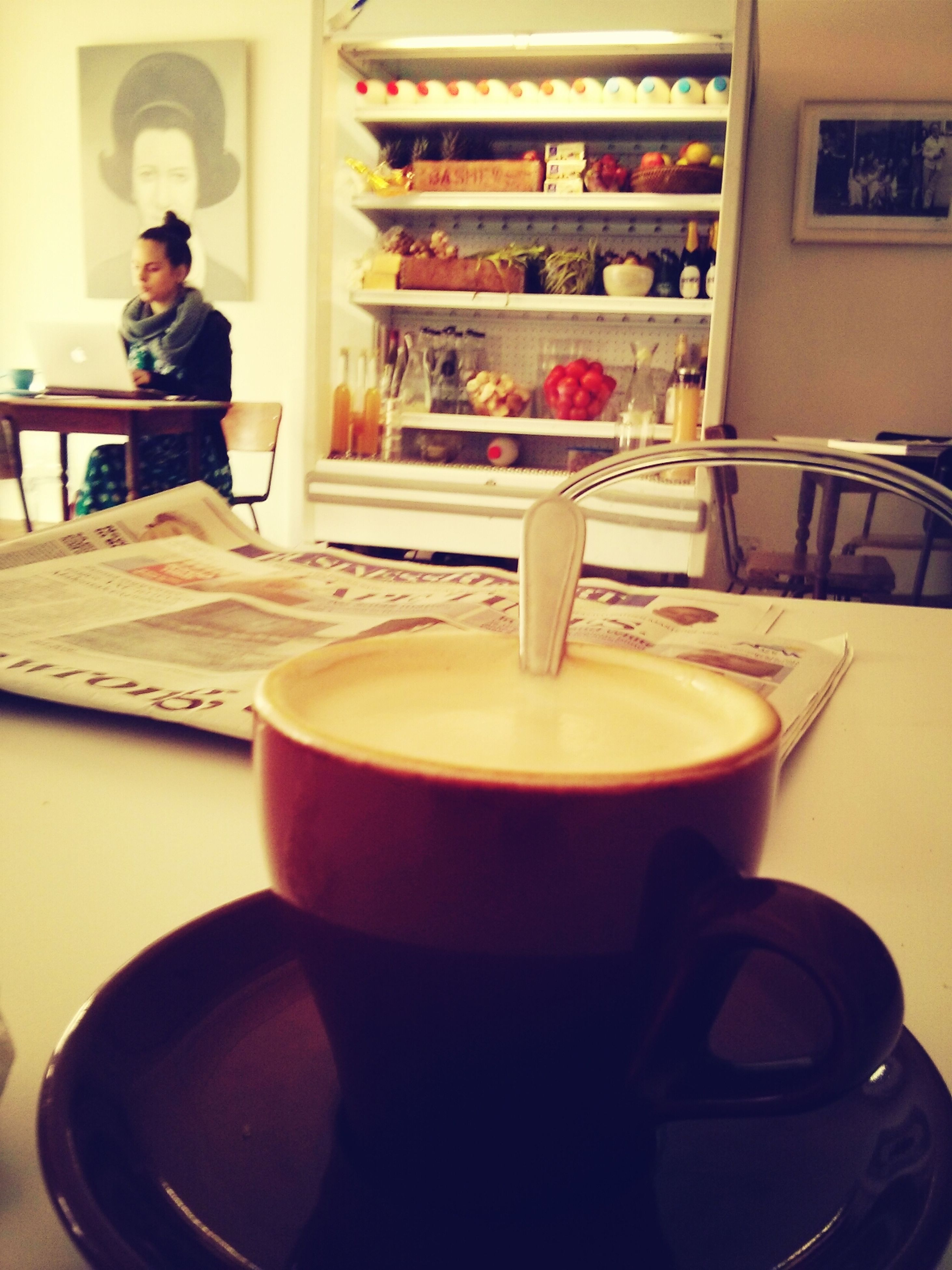 food and drink, indoors, drink, lifestyles, table, refreshment, sitting, coffee cup, leisure activity, casual clothing, coffee - drink, restaurant, freshness, food, holding, cafe, person