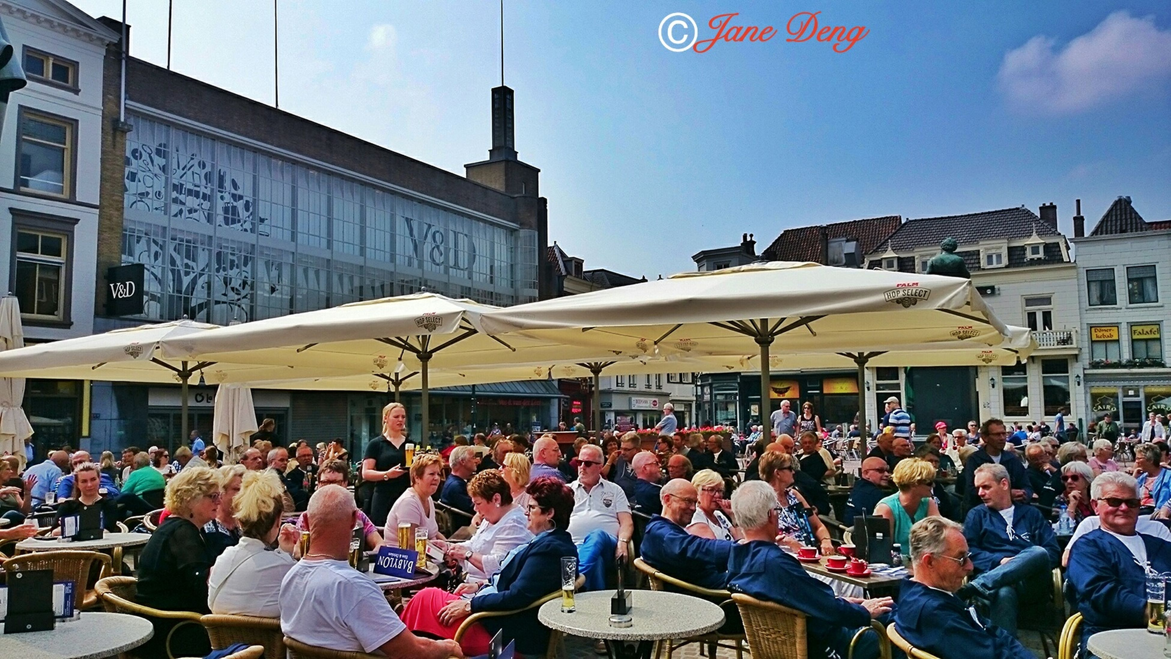 large group of people, building exterior, architecture, crowd, person, built structure, men, lifestyles, leisure activity, city, street, mixed age range, city life, sky, market, walking, day, outdoors, crowded