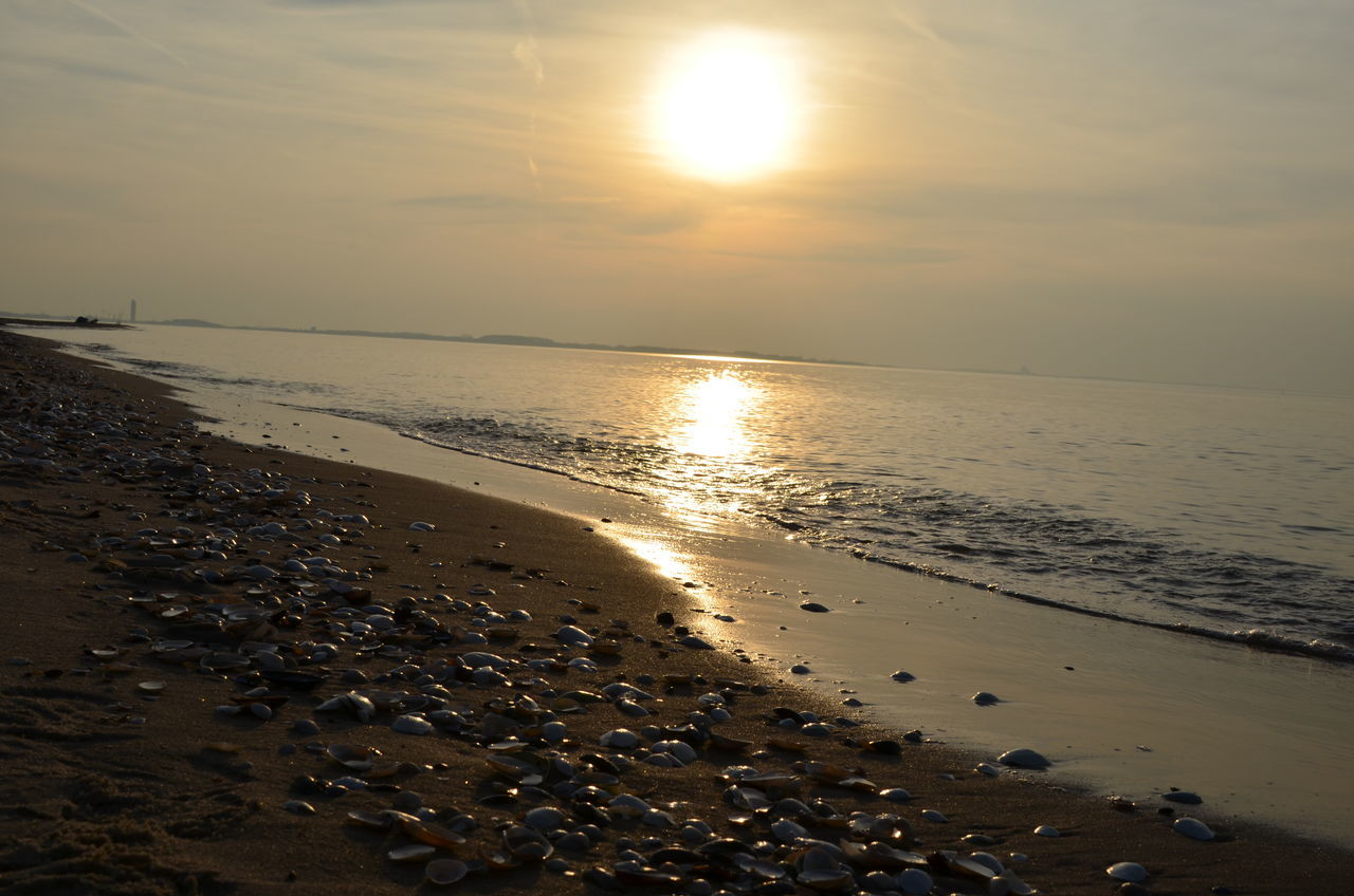 sea, sunset, beach, water, sun, shore, beauty in nature, sand, nature, scenics, horizon over water, sky, tranquil scene, tranquility, sunlight, idyllic, reflection, outdoors, no people, wave, day
