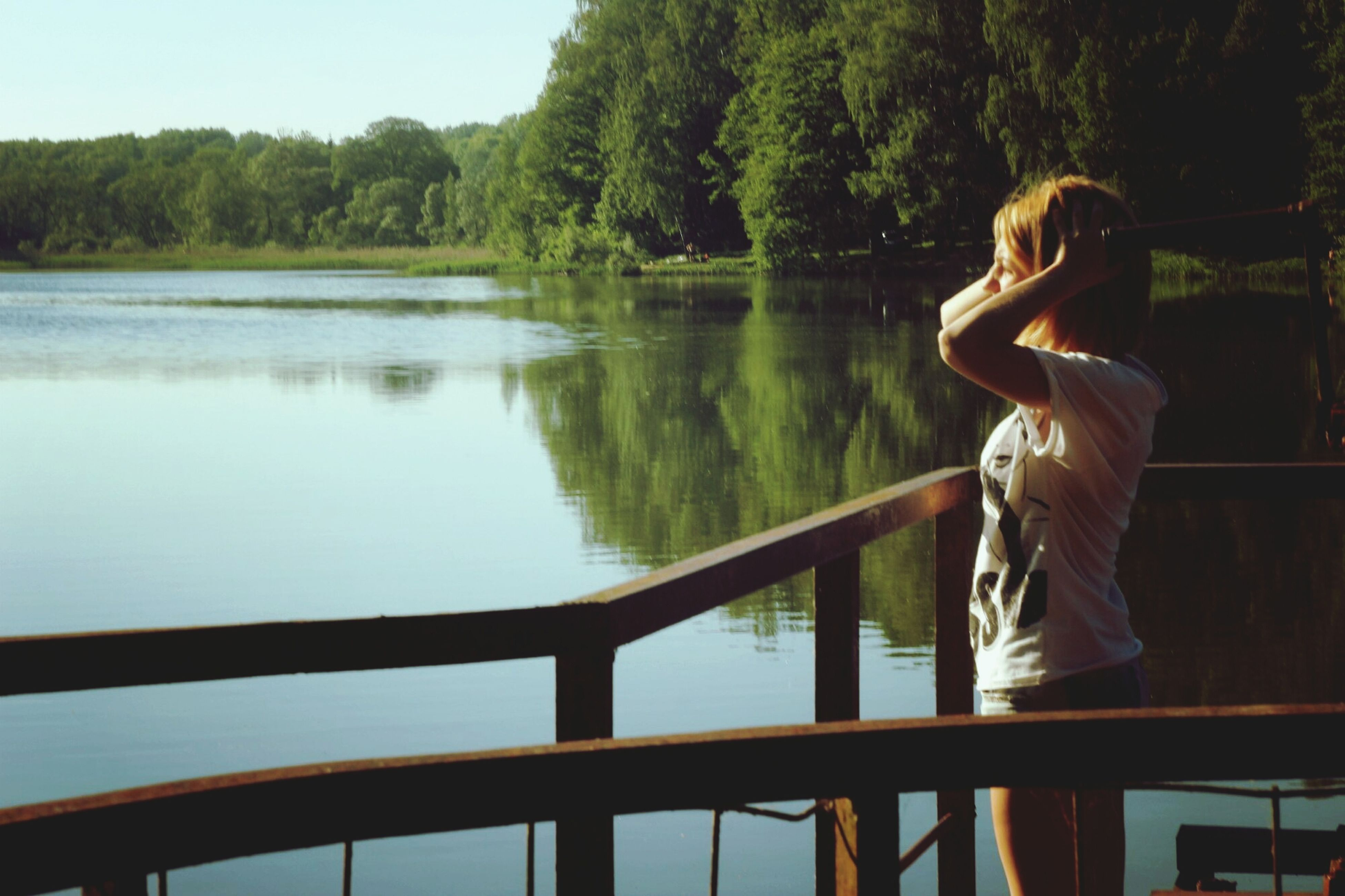water, tree, lake, railing, lifestyles, leisure activity, standing, river, tranquility, nature, reflection, rear view, casual clothing, tranquil scene, beauty in nature, full length, three quarter length, scenics