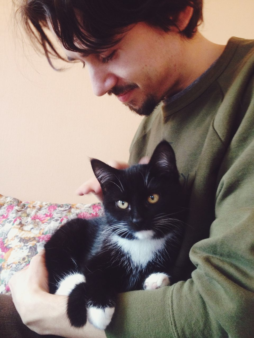 Young Man Holding Cat At Home