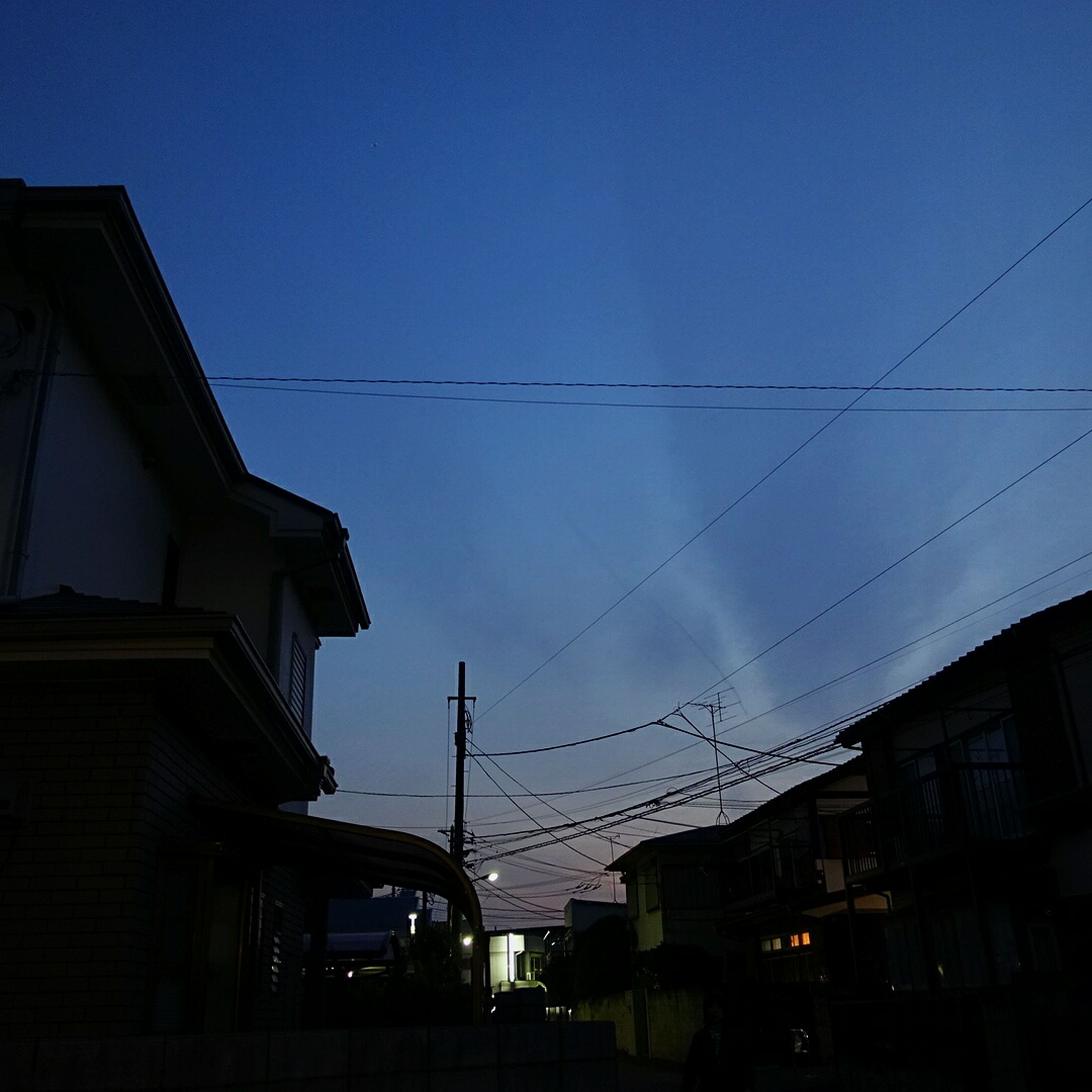 building exterior, architecture, built structure, power line, low angle view, transportation, cable, electricity pylon, city, sky, car, street, electricity, street light, clear sky, building, residential structure, residential building, dusk, silhouette