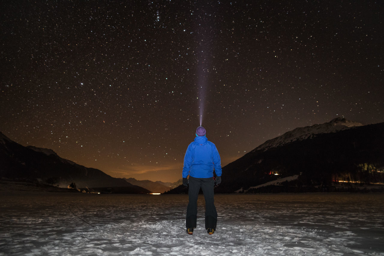 Adult Adults Only Adventure Astronomy Beauty In Nature Cold Temperature Discovery European Alps Frozen Lake Galaxy Headlamp Hiking Lake Light Ray Looking At View Milky Way Mountain Nature Night One Person Rear View Scenics Space Space And Astronomy Star - Space