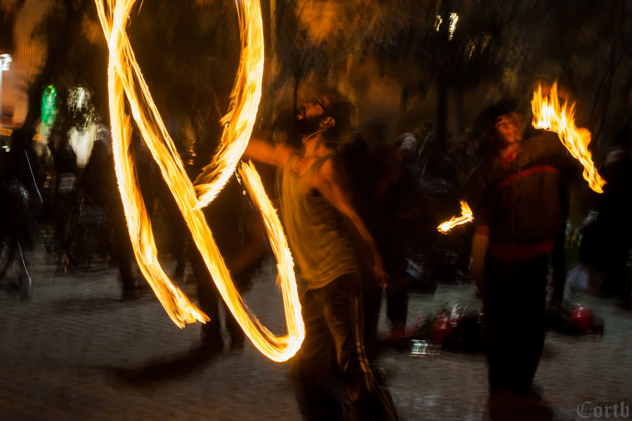 night, real people, flame, men, burning, women, leisure activity, performance, long exposure, blurred motion, heat - temperature, arts culture and entertainment, dancing, lifestyles, illuminated, motion, outdoors, togetherness, standing, full length, tree, young adult, adult, people