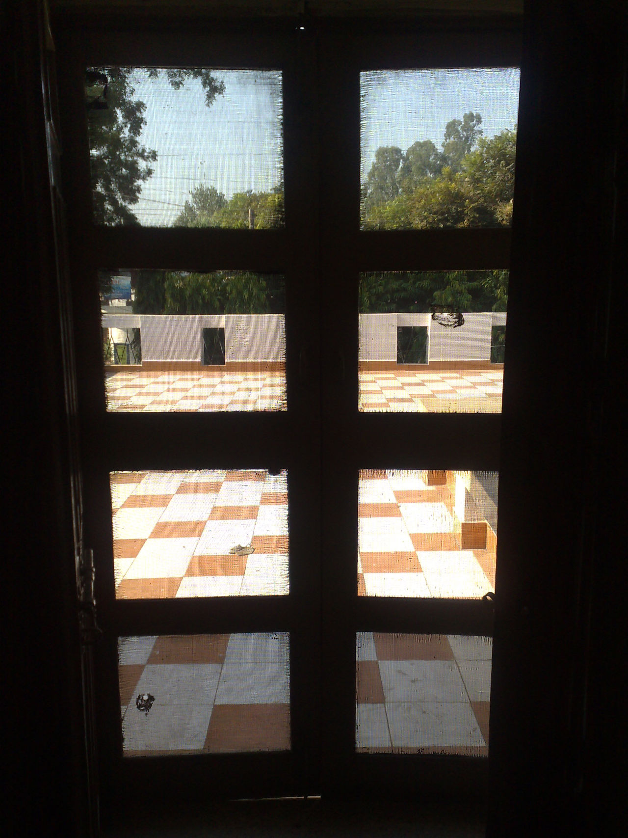The open courtyard with the sun shining on the courtyard, as well as trees and blue sky visible through the wire mesh set on the frame of a door Door Door Panels Home Interior House Indoors  Mesh Door Panels No People Outside View Transparent Window Window Frame