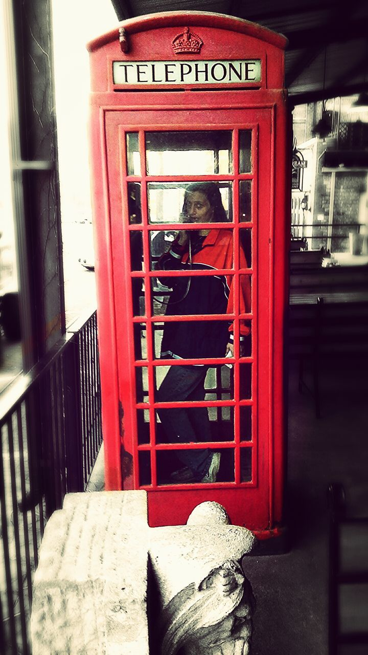 red, telephone booth, text, communication, day, built structure, building exterior, outdoors, pay phone, real people, architecture, one person, close-up, people