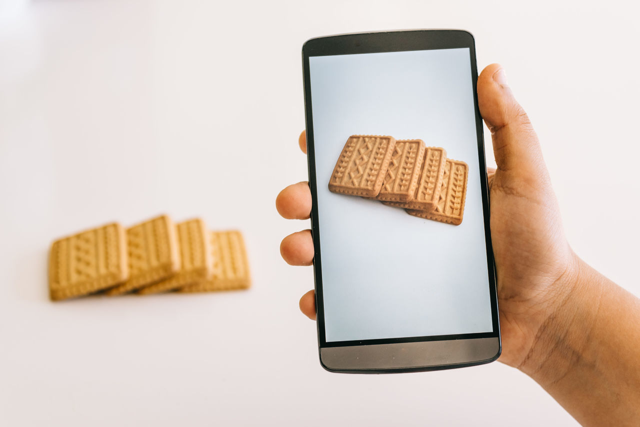 Cropped Hand Photographing Cookies Using Smart Phone Against White Background