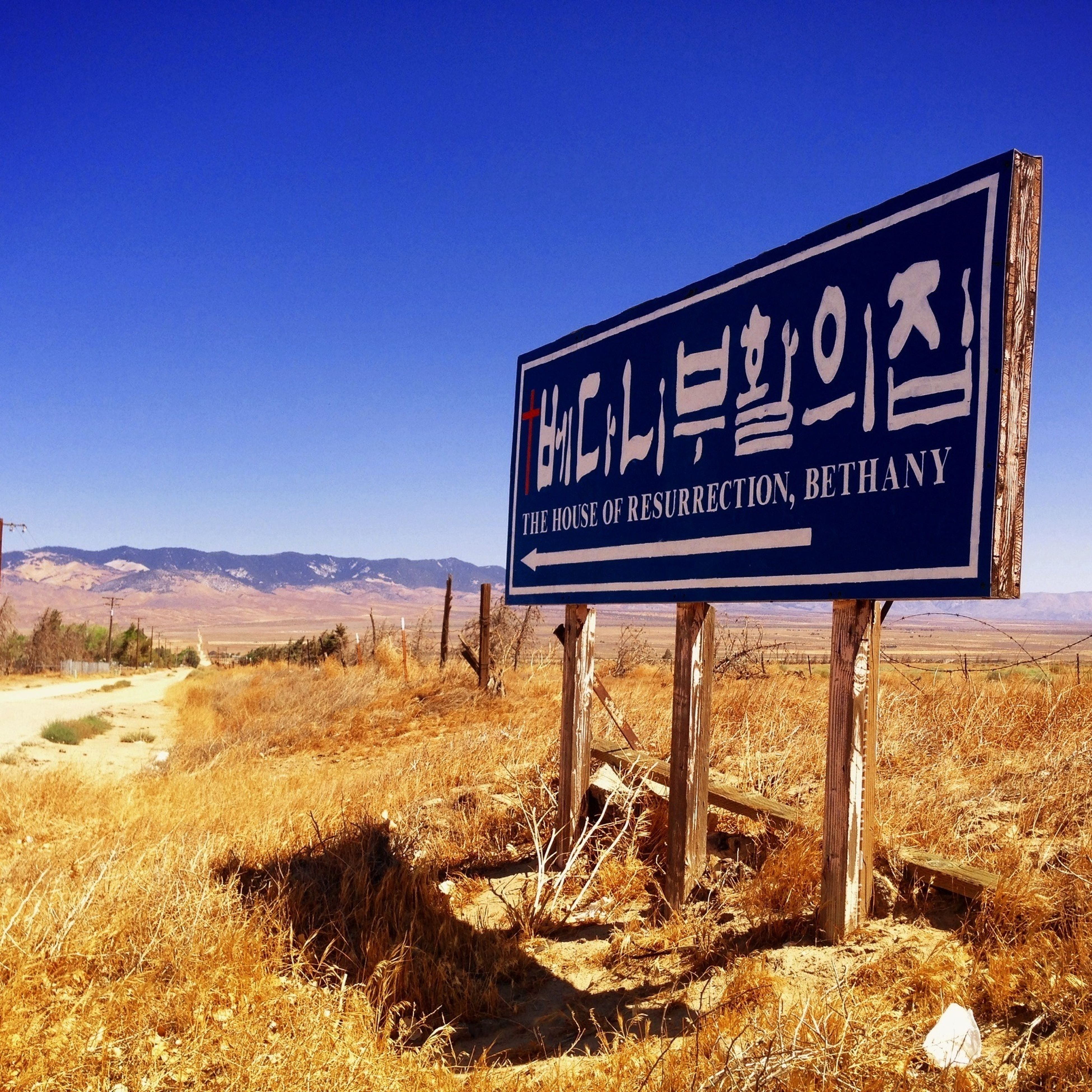 text, western script, clear sky, communication, blue, information sign, sign, copy space, guidance, information, road sign, landscape, capital letter, warning sign, field, nature, tranquility, non-western script, tranquil scene, day