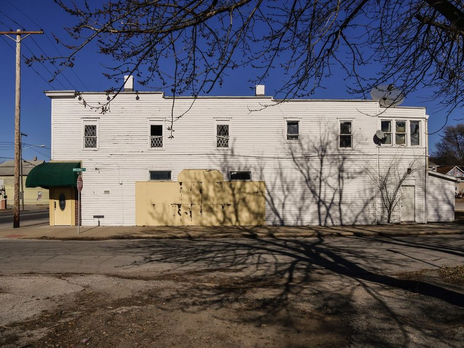 BUCKET SHOP in TATTERS ~ It looks like this Great Old Tavern and Restaurant will soon be a Vacant Lot Memory in the Southside of Saint Joseph, Missouri Building Exterior Architecture Built Structure Outdoors Tree Residential Building Bare Tree House Shadow No People Sky Day Nature Urban Exploration Cityscape Street Views Missouriphotography Kcac Artist Walker Evans Relicsofthepast Saint Joseph Clear Sky Frozen In Time Tavern  Bucket Shop