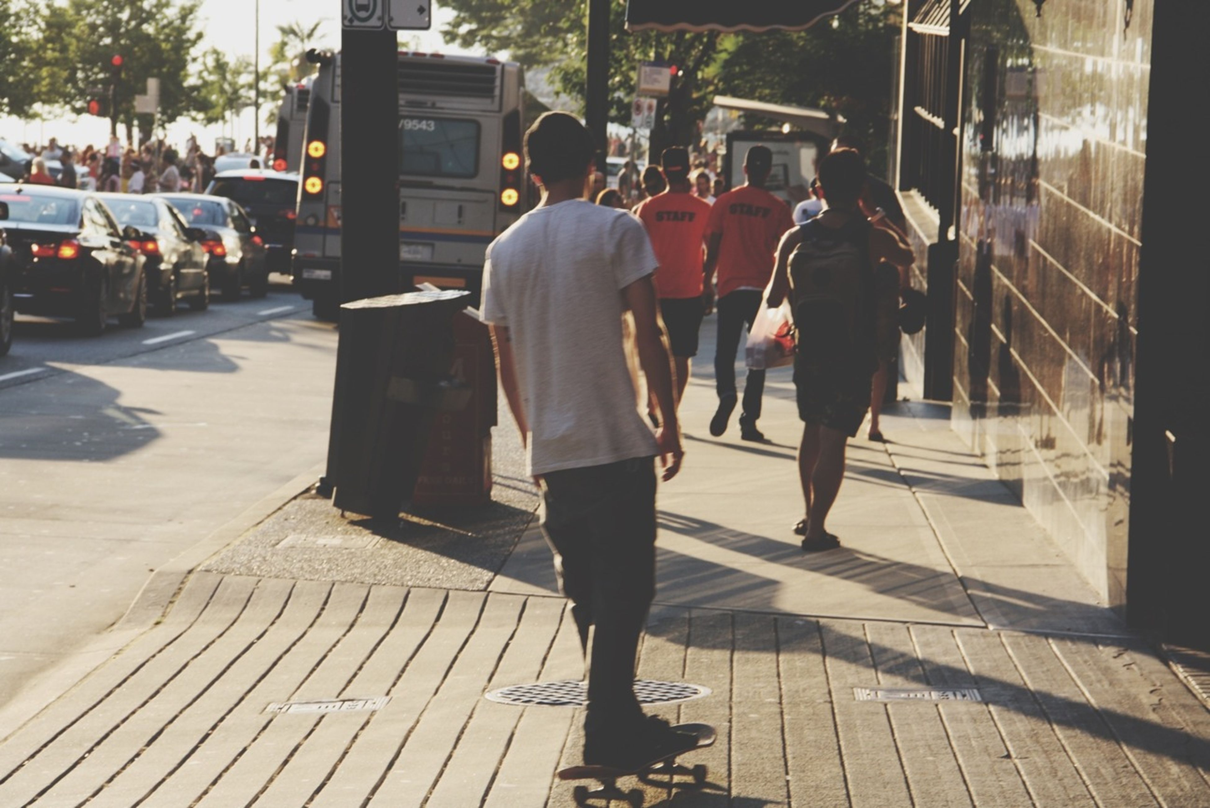 men, lifestyles, walking, street, rear view, person, city life, city, full length, leisure activity, sidewalk, sunlight, building exterior, shadow, togetherness, outdoors, casual clothing, day