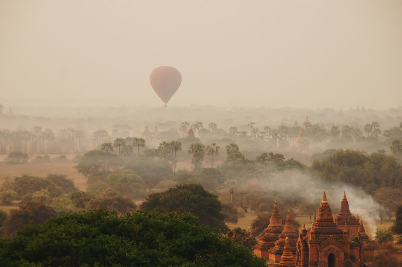 hot air balloon, religion, fog, ancient, architecture, tree, nature, pagoda, sky, travel destinations, landscape, built structure, history, no people, spirituality, mid-air, outdoors, place of worship, dawn, scenics, beauty in nature, building exterior, flying, ancient civilization, day