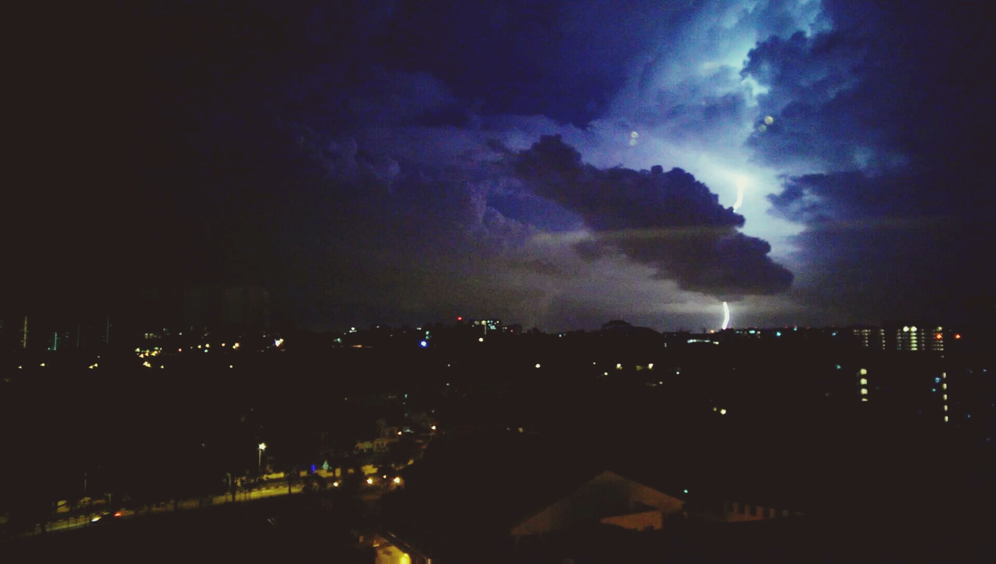 illuminated, night, building exterior, architecture, sky, city, built structure, cityscape, cloud - sky, residential building, residential district, dusk, residential structure, light - natural phenomenon, city life, lightning, storm cloud, outdoors, dark, thunderstorm