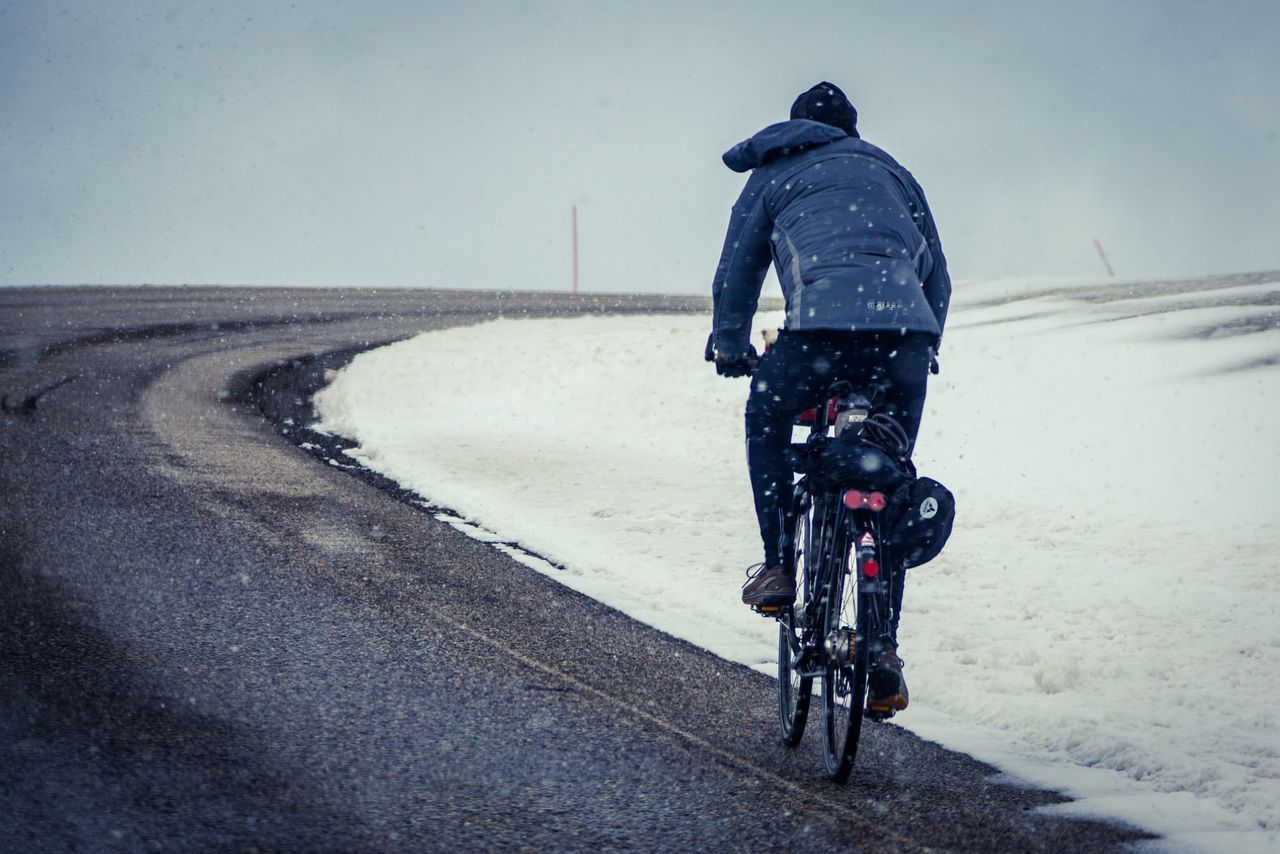Bicycle Cold Temperature Cycling Day Full Length Lifestyles Men Nature Nordkapp Norway One Person Outdoors People Real People Rear View Riding Road Sky Snow Transportation Winter