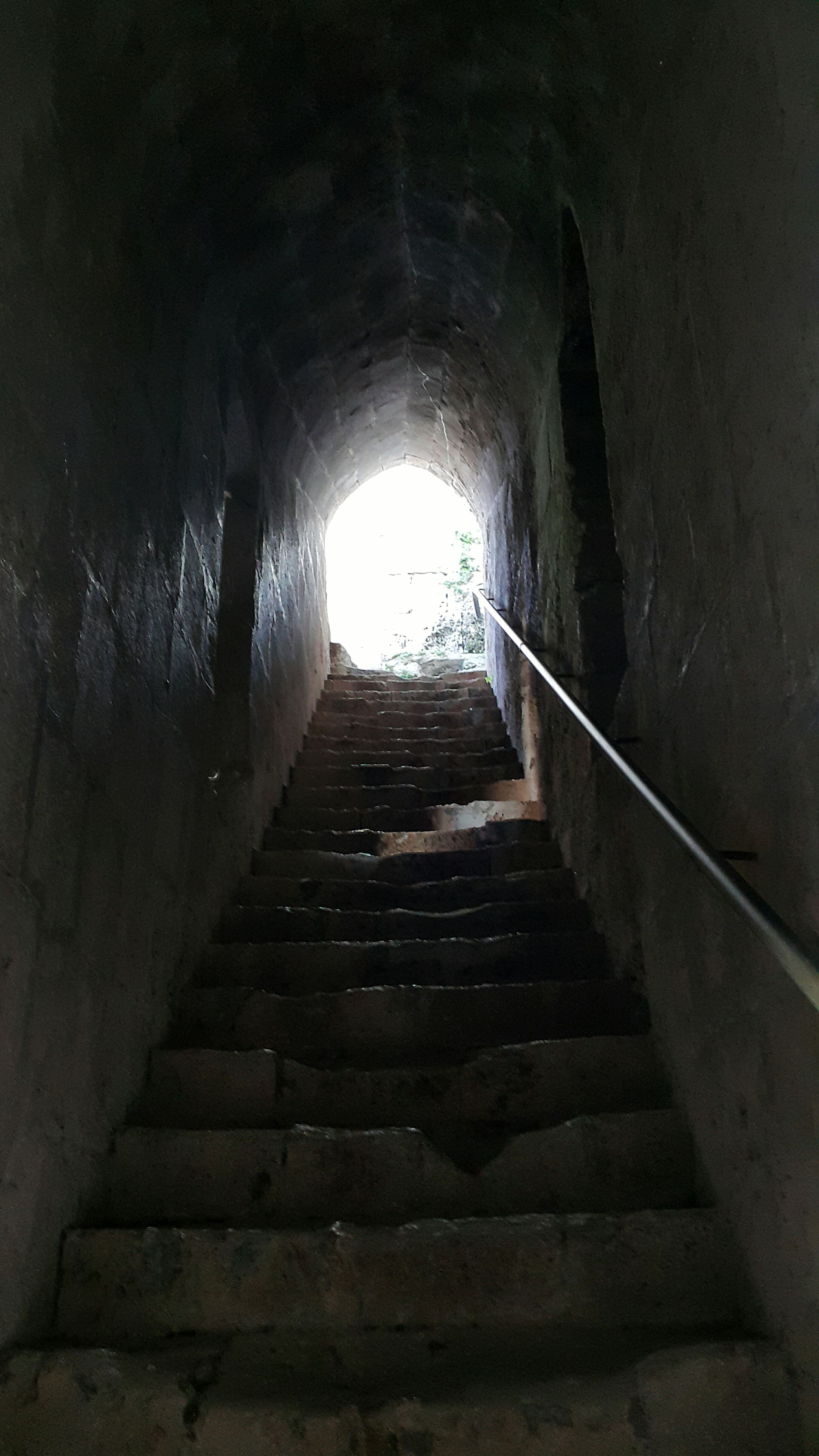 the way forward, architecture, steps, indoors, built structure, steps and staircases, staircase, tunnel, diminishing perspective, wall - building feature, arch, railing, vanishing point, old, low angle view, narrow, building, sunlight, light at the end of the tunnel, stairs