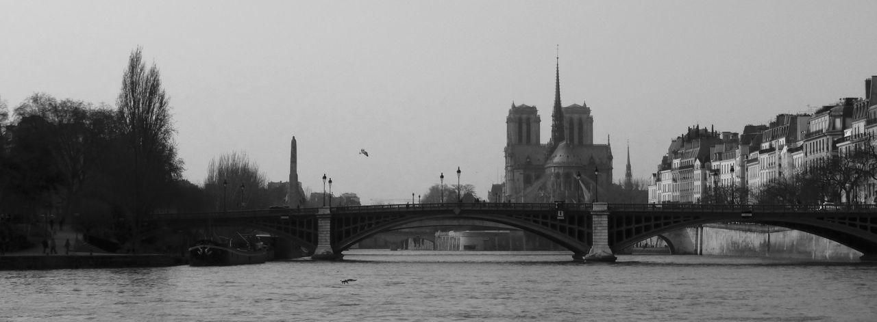 Arch Bridge Over Seine River Against Notre Dame De Paris