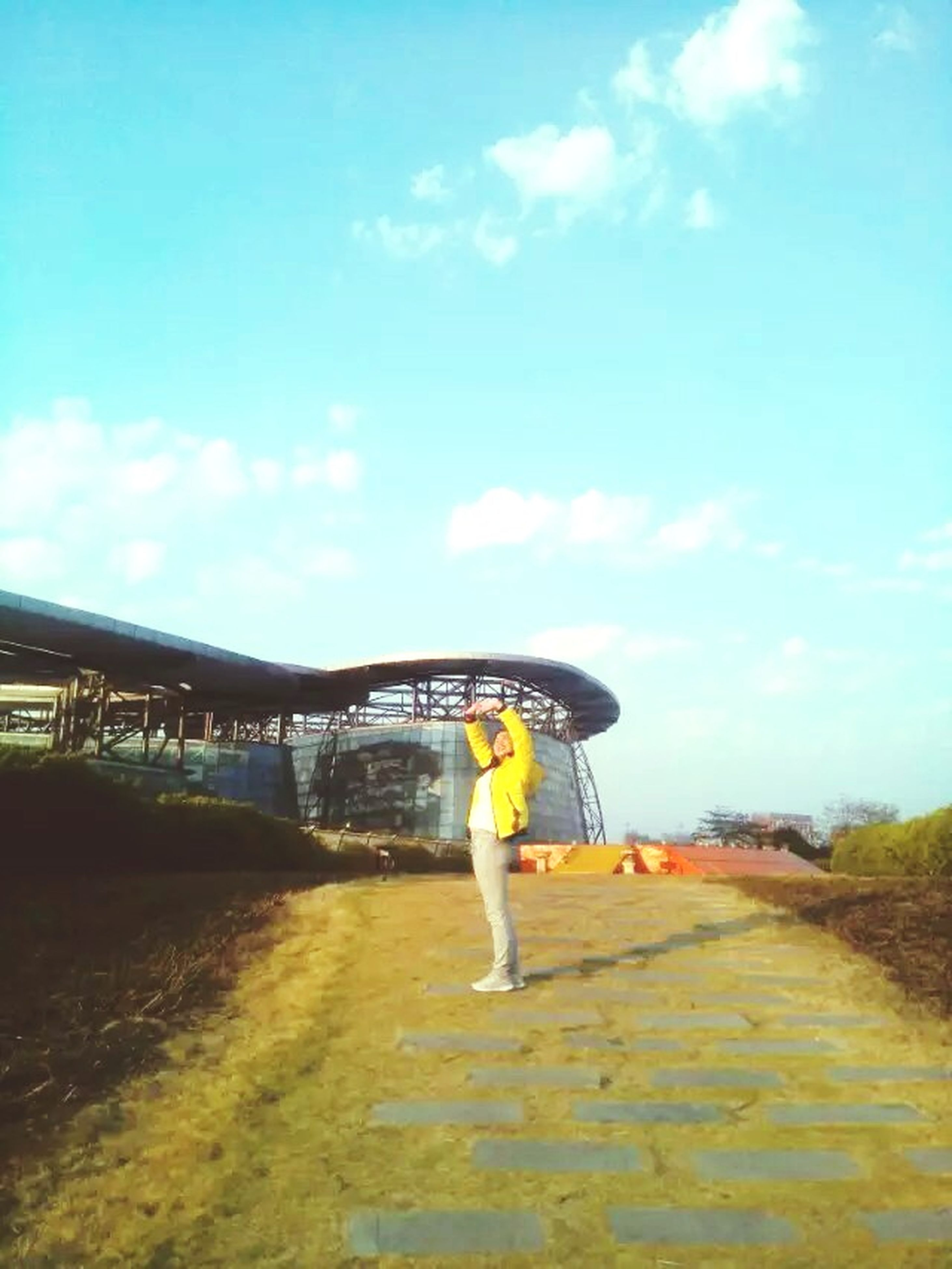 full length, lifestyles, sky, leisure activity, walking, rear view, men, cloud - sky, casual clothing, standing, the way forward, road, transportation, bridge - man made structure, person, outdoors, cloud, built structure