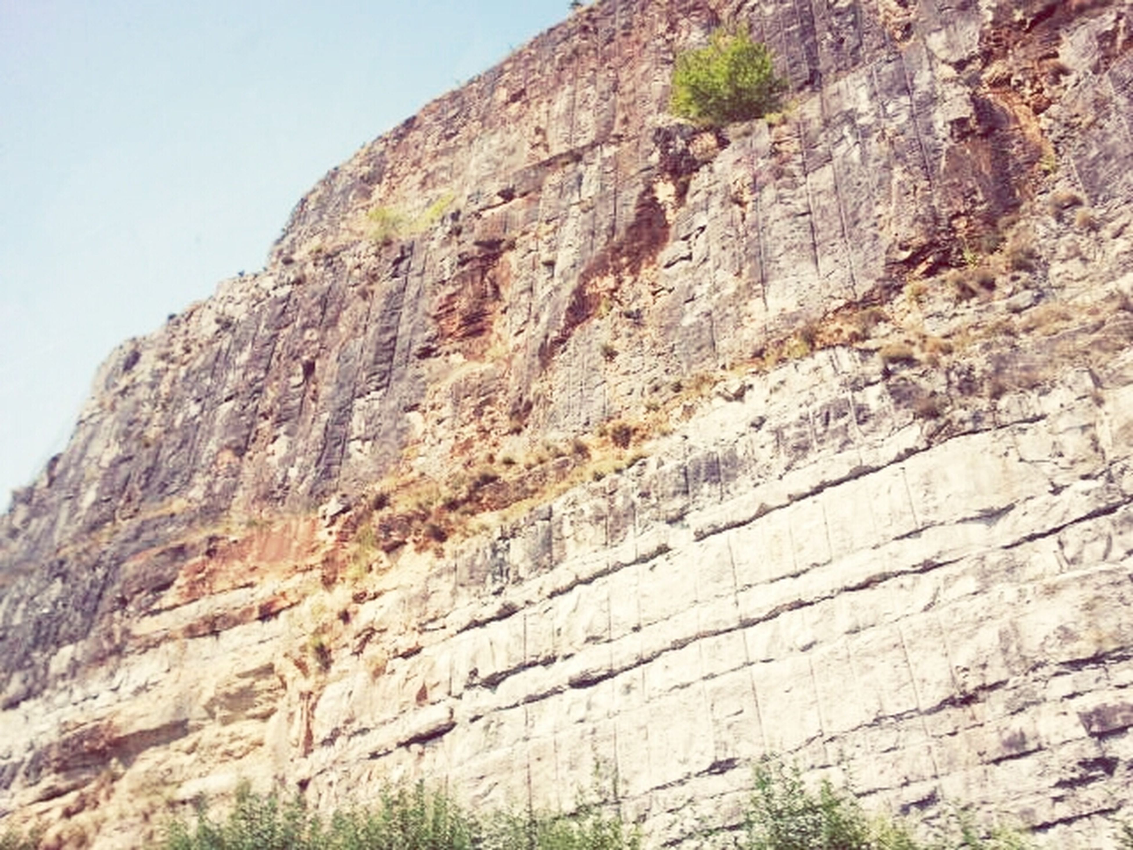 mountain, low angle view, rock formation, clear sky, rock - object, sky, tranquility, nature, rough, rocky mountains, tranquil scene, beauty in nature, day, textured, scenics, non-urban scene, tree, outdoors, geology, landscape