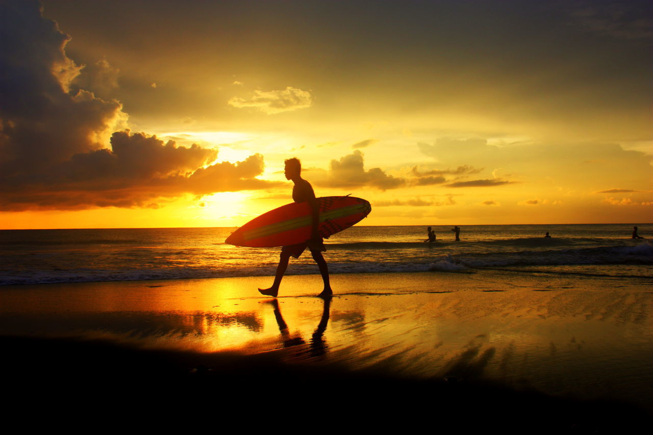 Man Carrying Surfboard On Shore At Beach Against Sky During Sunset