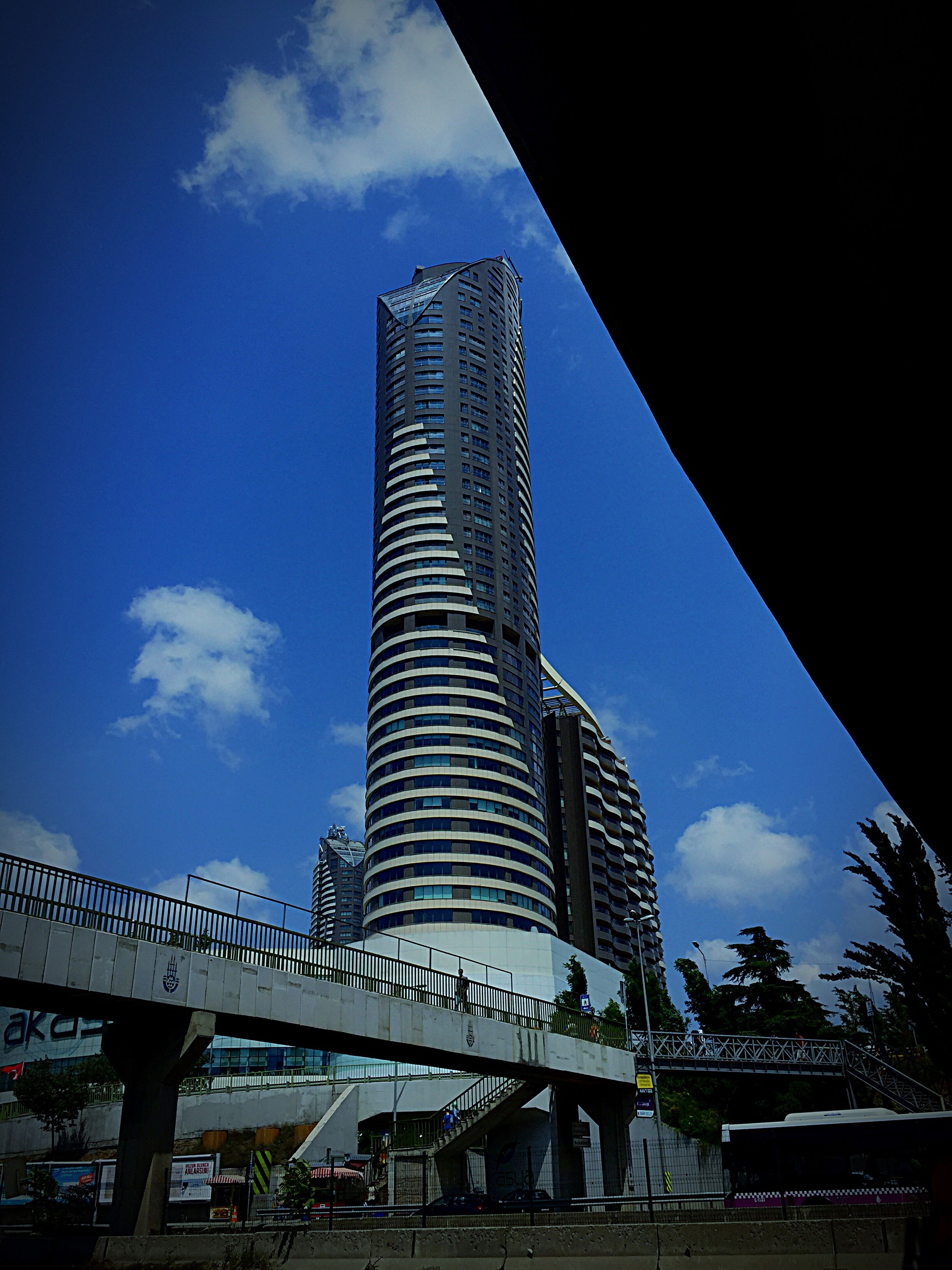 low angle view, architecture, built structure, blue, sky, building exterior, skyscraper, tall - high, city, tower, tall, modern, office building, outdoors, cloud - sky, travel destinations, day, engineering, architectural feature, building story, city life, capital cities