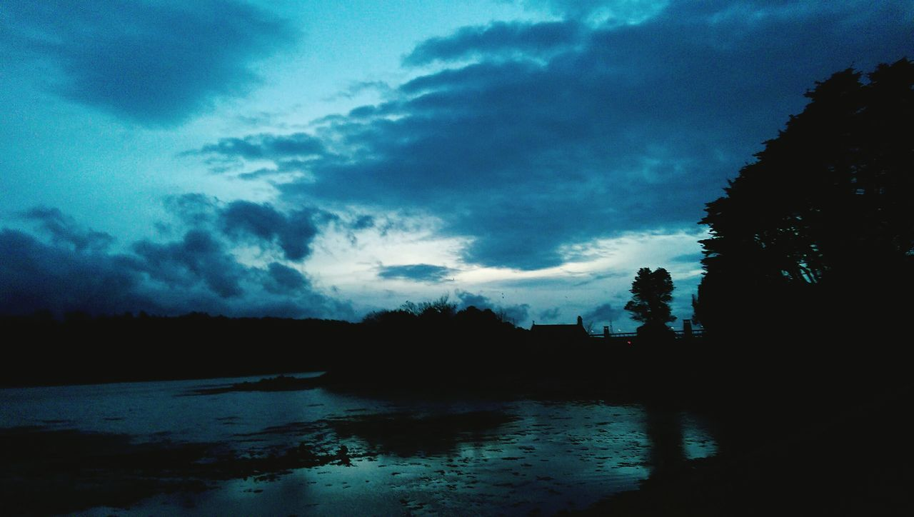 tree, sky, cloud - sky, silhouette, water, no people, nature, tranquility, weather, tranquil scene, scenics, beauty in nature, reflection, landscape, outdoors, winter, storm cloud, day