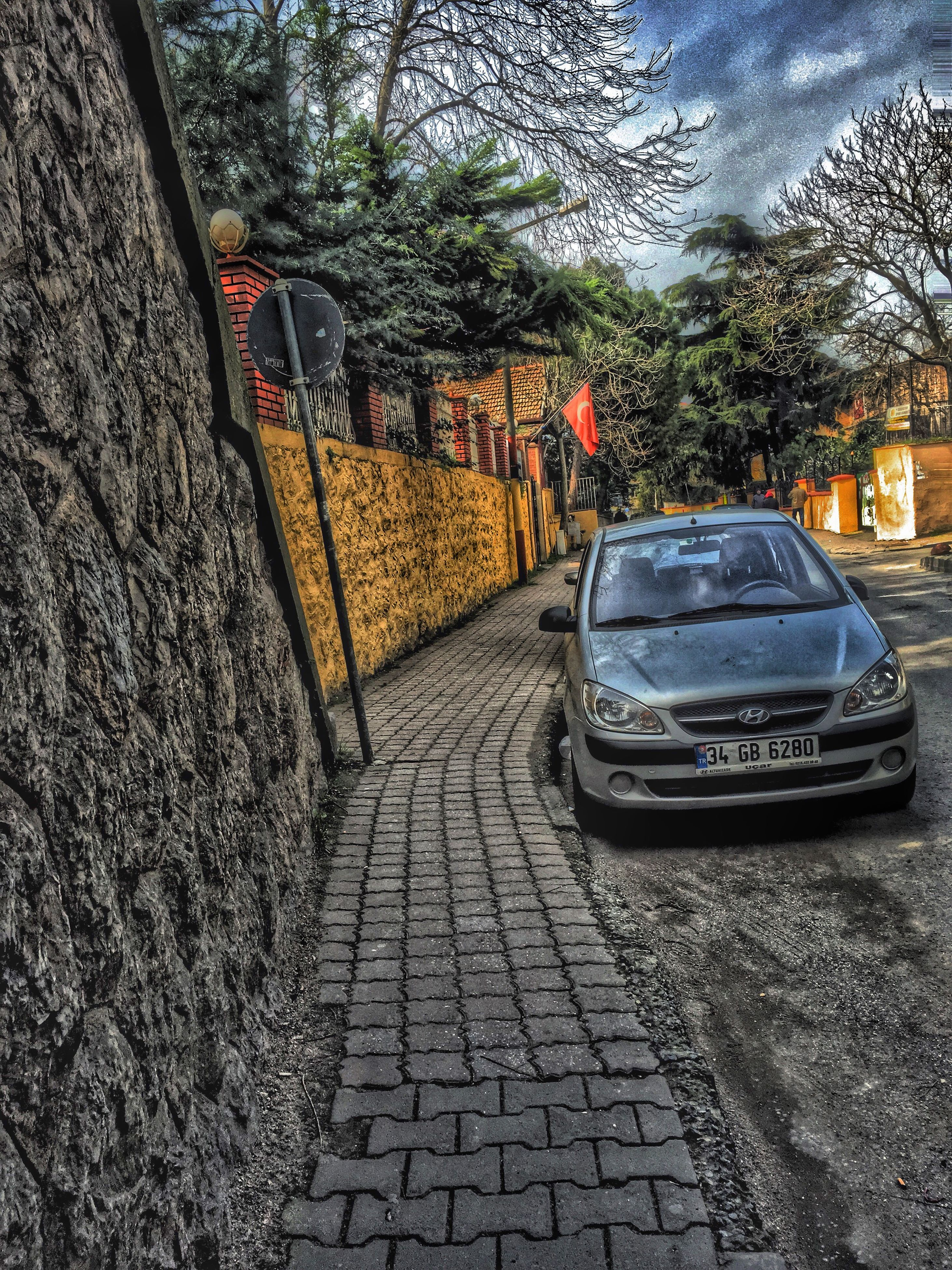 transportation, mode of transport, tree, land vehicle, building exterior, street, car, built structure, architecture, cobblestone, the way forward, parking, parked, sidewalk, day, stationary, outdoors, footpath, road, autumn