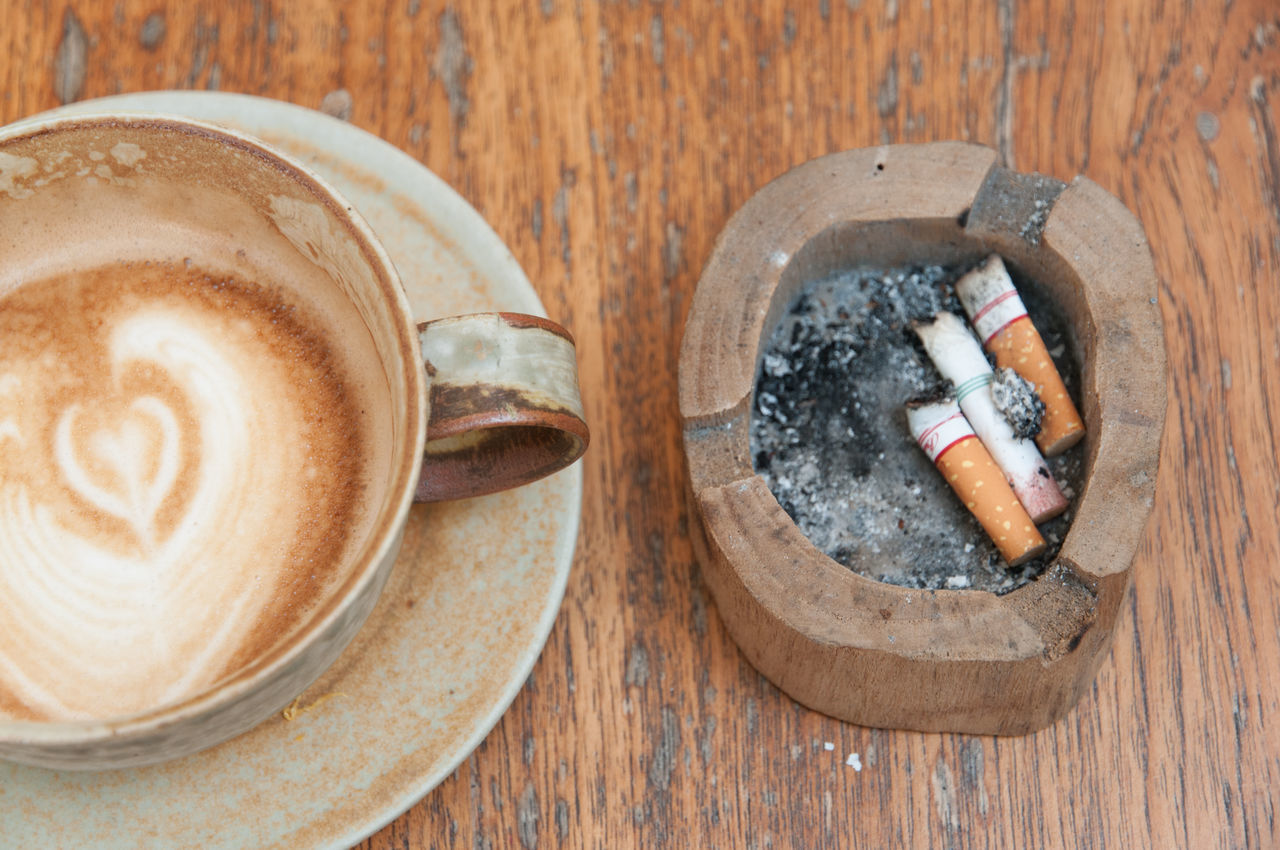 A cup of coffee with cigarette on wooden background Cigarette  Cigarette Time Close-up Coffee Day Hot Latte No People Wooden