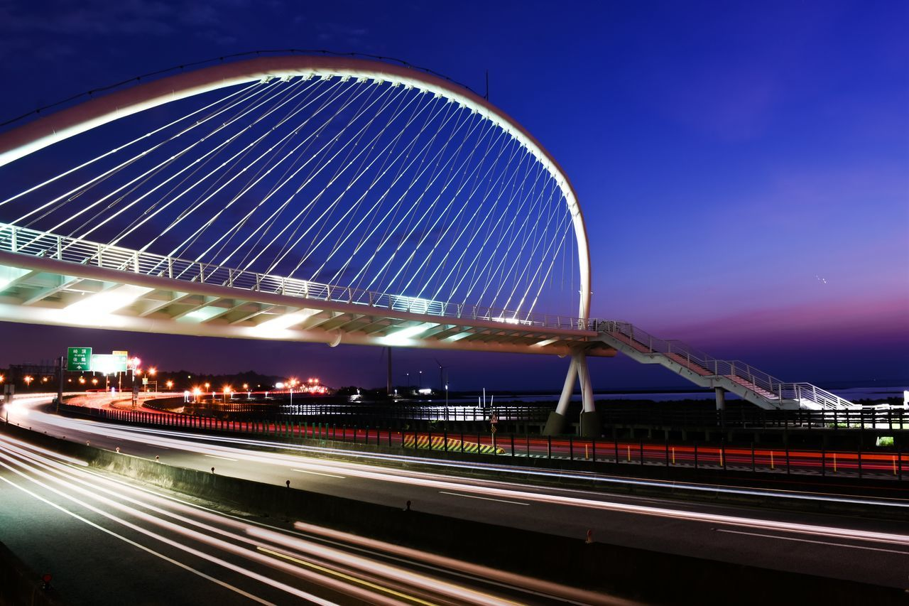 illuminated, night, light trail, motion, architecture, long exposure, built structure, speed, bridge - man made structure, no people, outdoors, amusement park, sky, clear sky, building exterior, city, high street