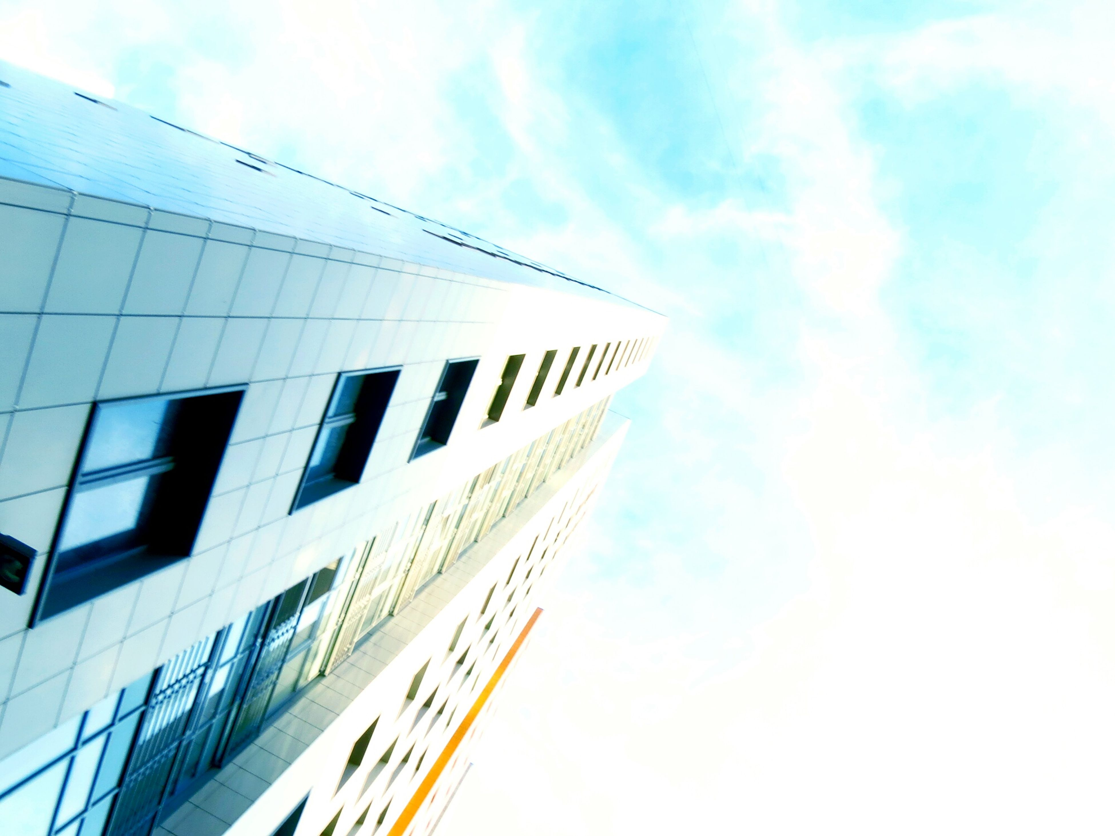 low angle view, architecture, building exterior, built structure, sky, modern, building, office building, city, tall - high, skyscraper, day, cloud - sky, tower, cloud, outdoors, no people, blue, in a row, tall
