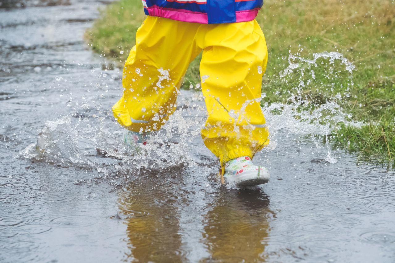 Jumping up and down in muddy puddles // Childhood Day Fun Jumping Low Section Motion Muddy Nature One Girl Only One Person Outdoors People Playful Puddle Rain Real People Reflection Relection On Water Rubber Boot Splashing Torrential Rain Water Wet Yellow