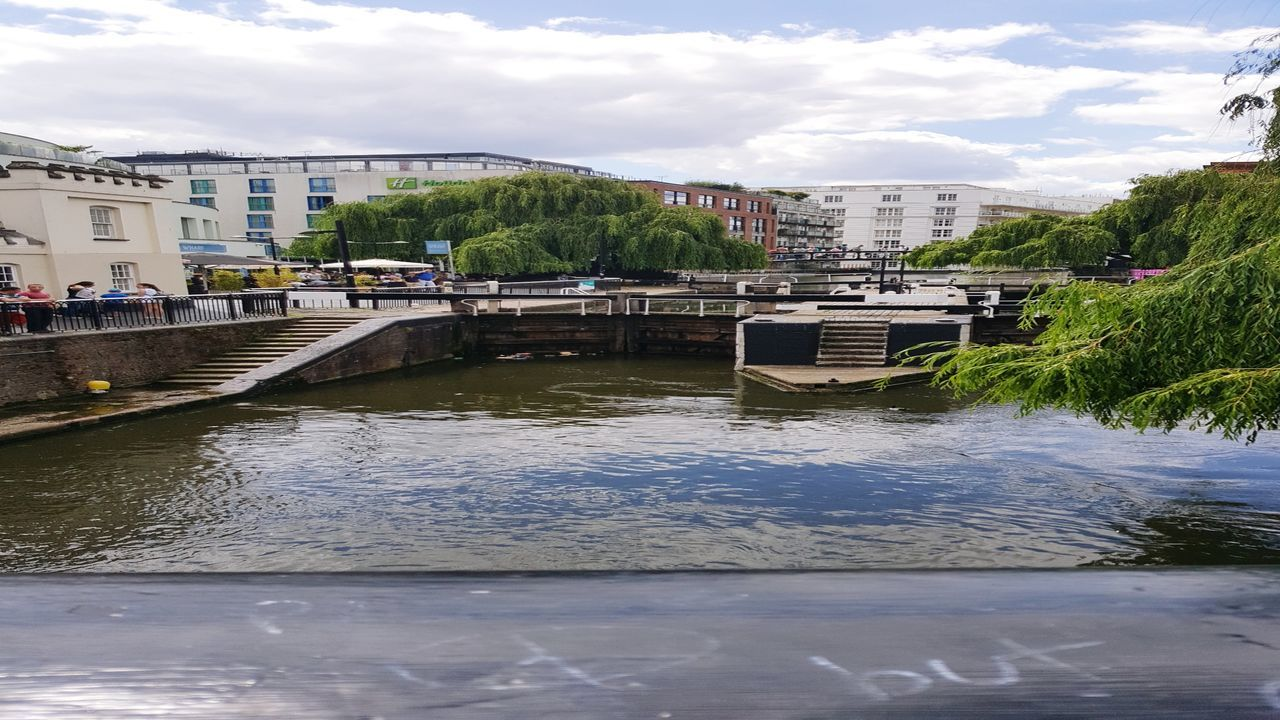 architecture, built structure, water, building exterior, river, cloud - sky, city, waterfront, bridge - man made structure, sky, connection, day, transportation, outdoors, residential building, no people, tree, nature, nautical vessel, cityscape