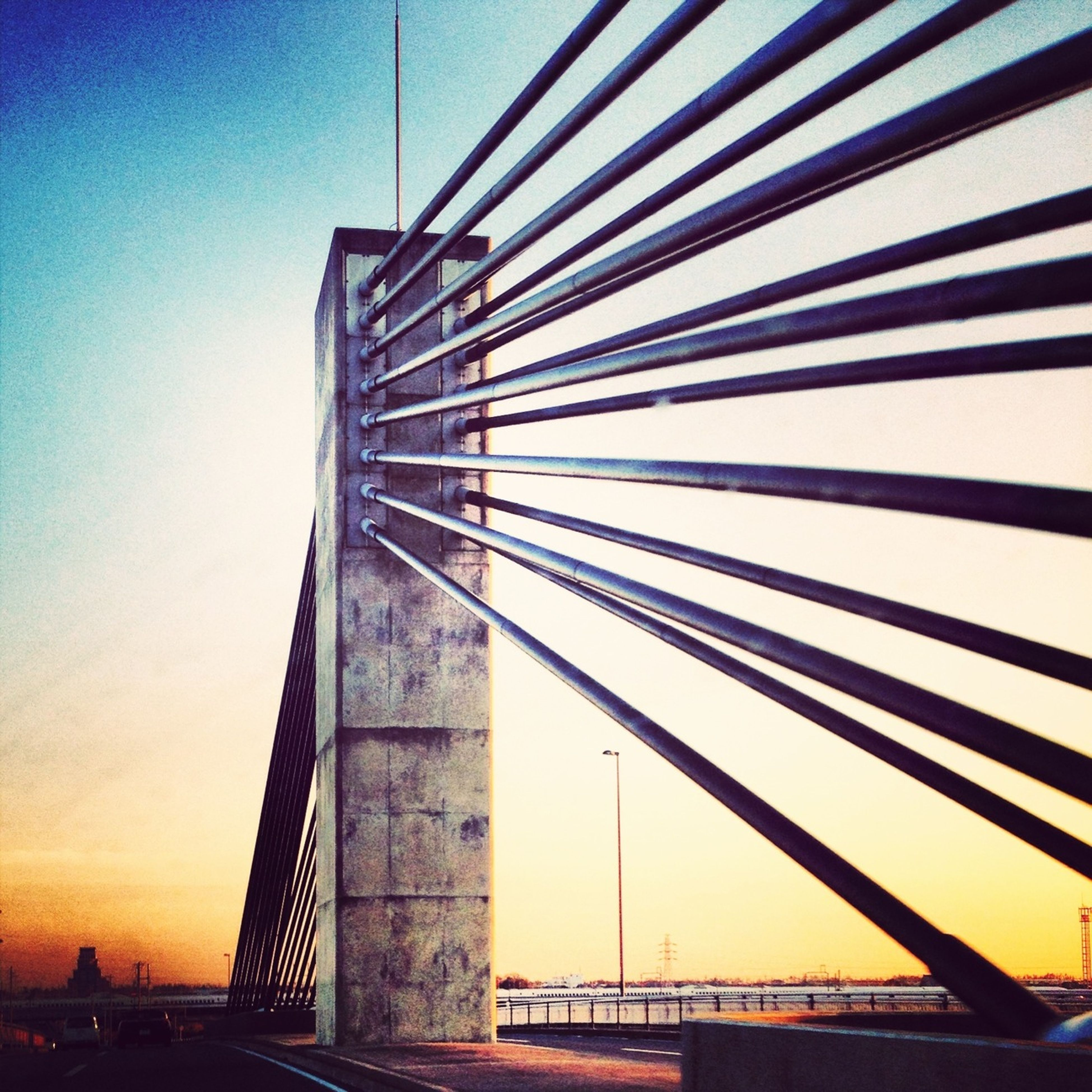 built structure, architecture, low angle view, modern, bridge - man made structure, engineering, connection, sunset, clear sky, sky, building exterior, sunlight, bridge, suspension bridge, tall - high, city, railing, outdoors, silhouette, no people