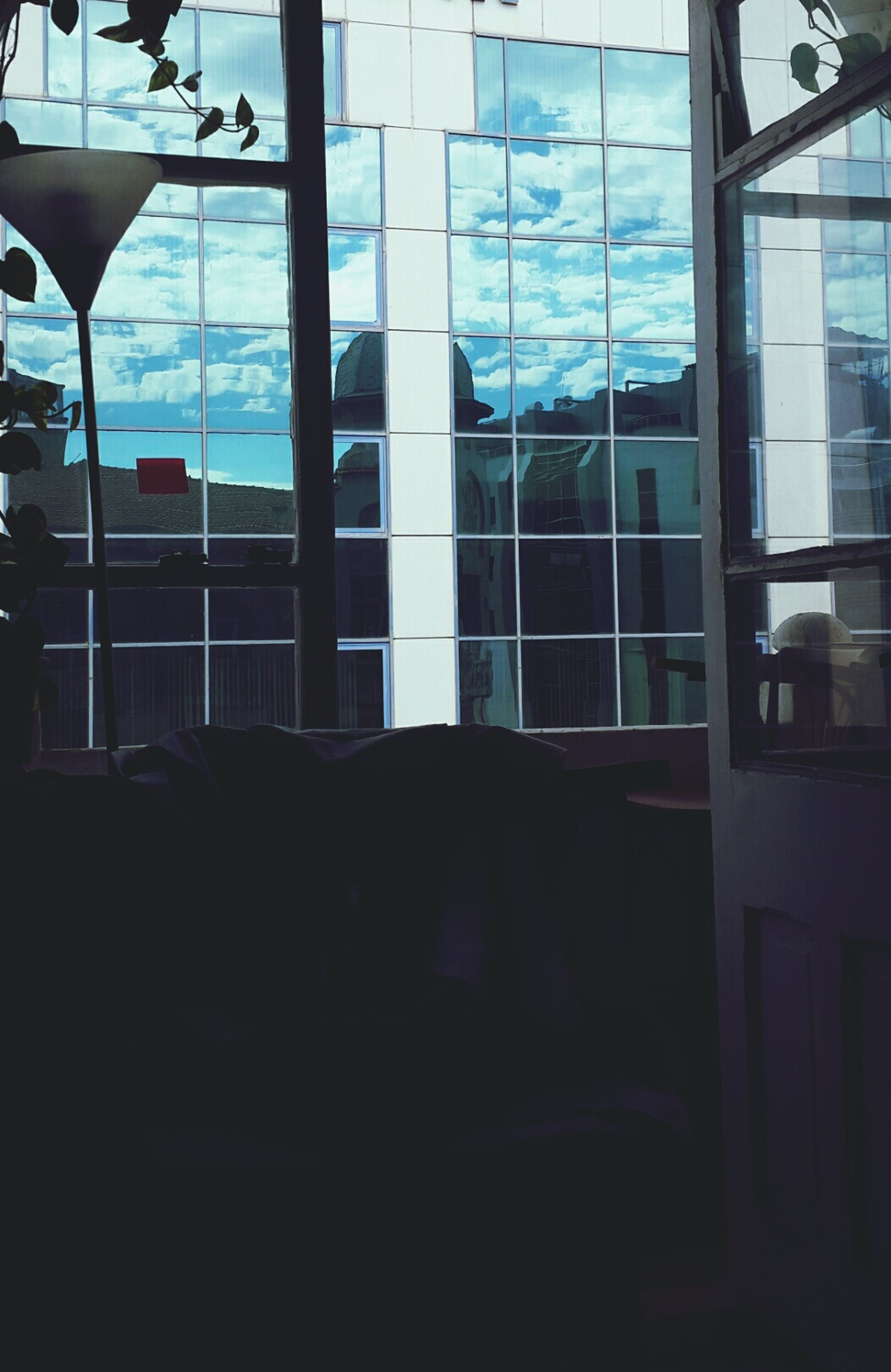 window, glass - material, indoors, architecture, built structure, transparent, building exterior, building, glass, reflection, sunlight, day, looking through window, house, city, home interior, modern, residential building, curtain, sky