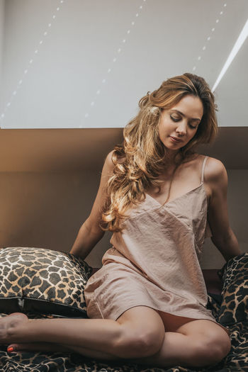 Portrait of a young female at morning in her bedroom 30s Beautiful Beautiful Woman Beauty In Nature Bed Day Home Interior Indoors  Indoors  Lifestyle Lifestyles Lifestzle Morning Nightie One Person Portrait Real People Roof Room Shadow Sitting Water Young Women