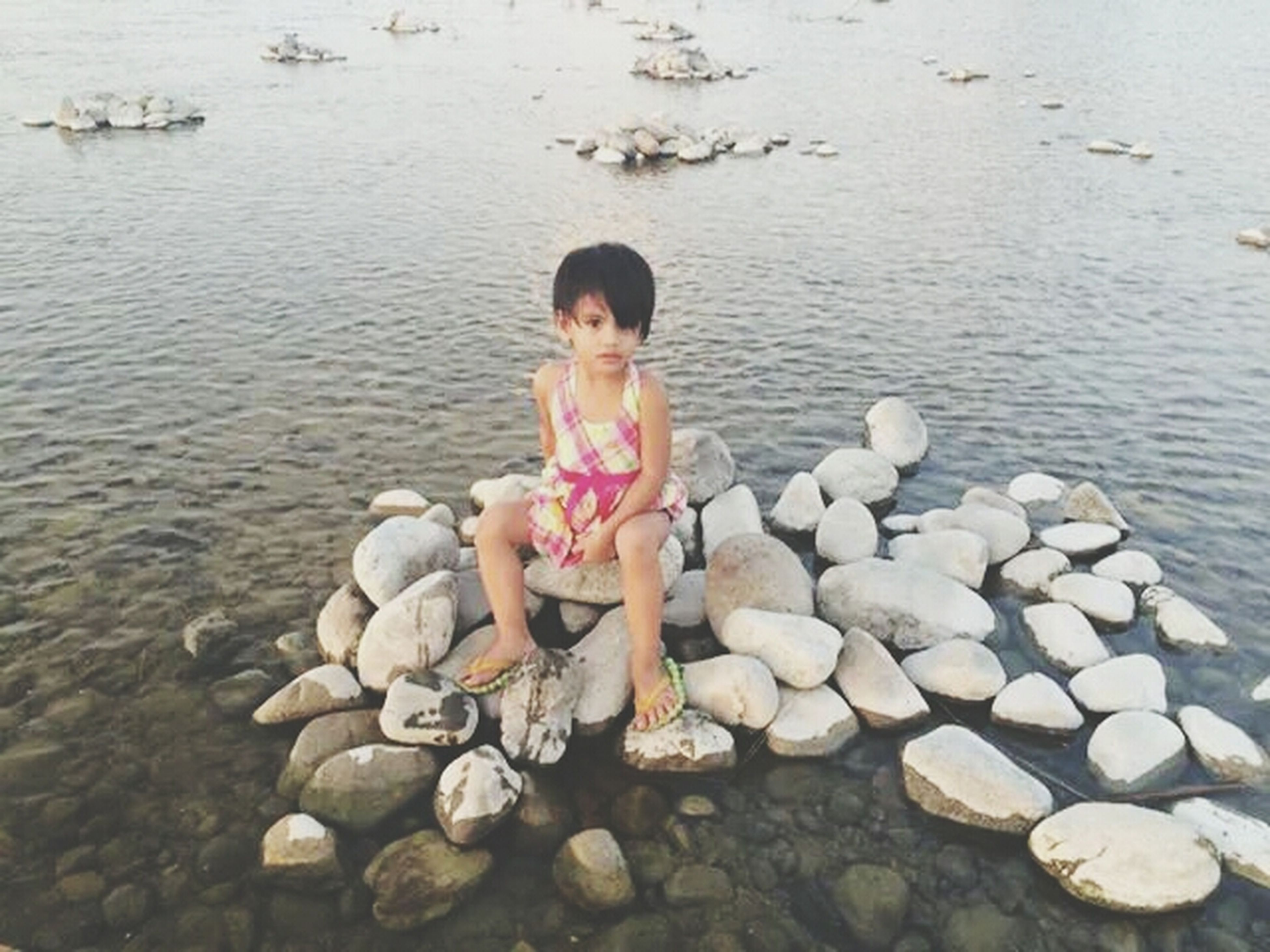 water, lifestyles, leisure activity, casual clothing, childhood, full length, person, boys, elementary age, standing, rock - object, stone - object, girls, high angle view, beach, nature, day, pebble