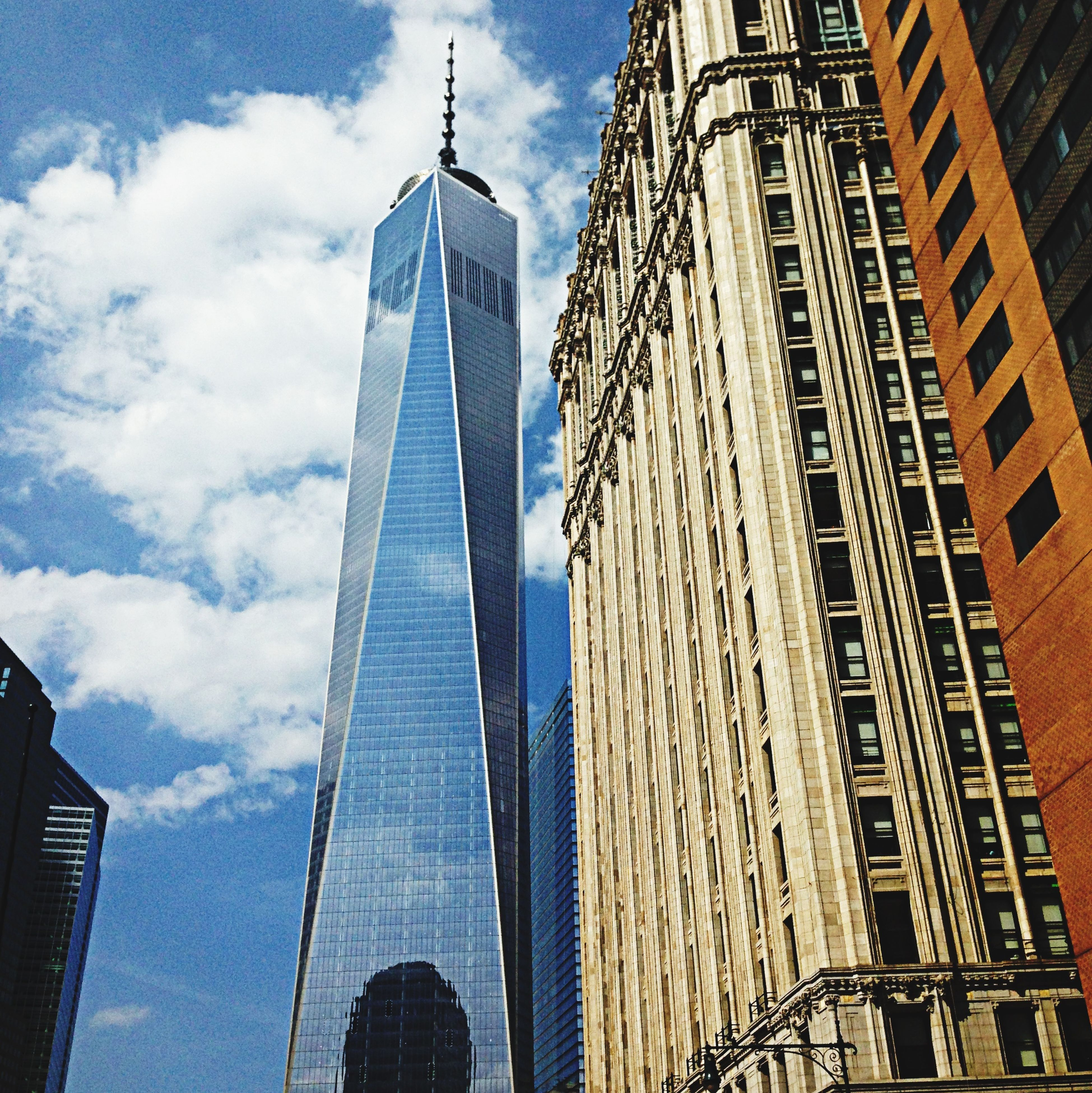 architecture, skyscraper, building exterior, tall - high, built structure, tower, modern, city, office building, low angle view, capital cities, sky, financial district, famous place, travel destinations, international landmark, tall, reflection, glass - material, cloud - sky