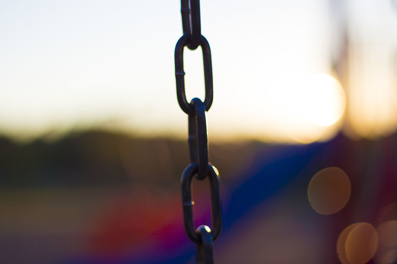Close-Up Of Chain Against On Field Sky During Sunset