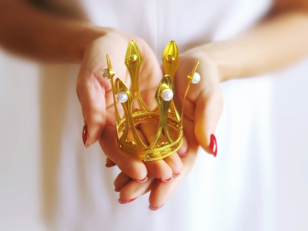 Human Hand One Person Holding Indoors  Human Body Part Close-up Women Real People Dreaming People Princess Gold Pearls Queen White Background Nail Polish Crown Beautiful Romantic Romance Selective Focus Lovely Rich Royal Childhood Place Of Heart