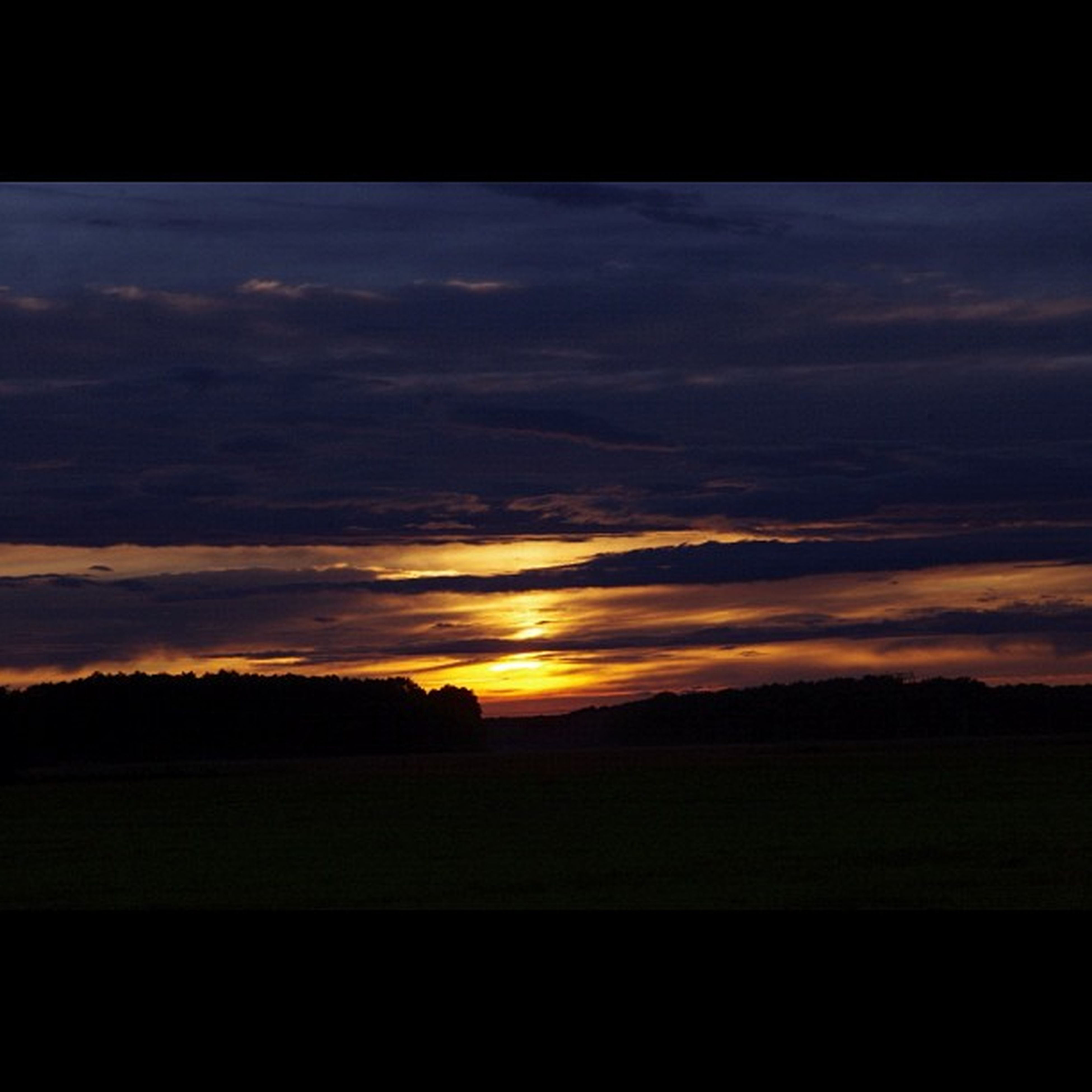 sunset, scenics, tranquil scene, sky, tranquility, beauty in nature, silhouette, landscape, cloud - sky, orange color, nature, idyllic, cloud, dramatic sky, cloudy, dark, moody sky, horizon over land, outdoors, non-urban scene