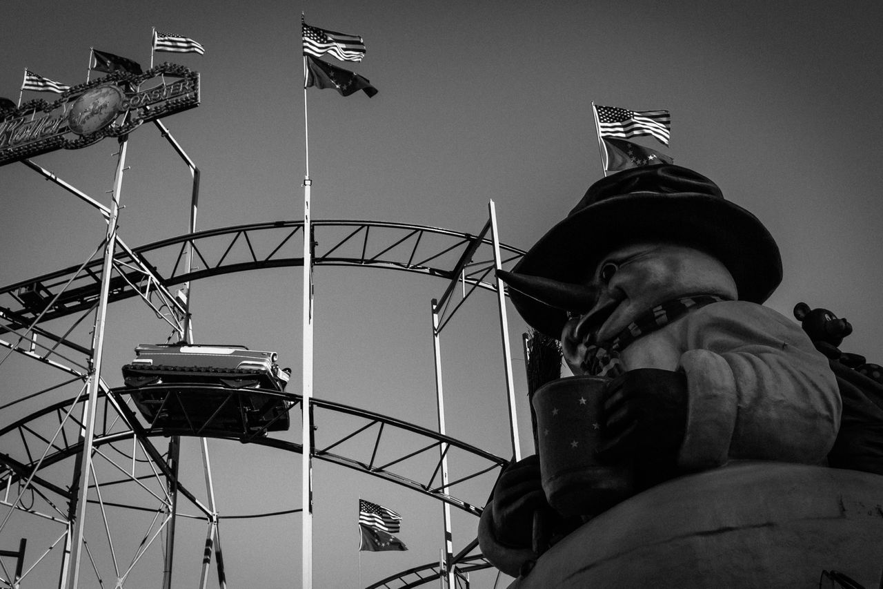 Low Angle View Of Rollercoaster And American Flag Over Statue