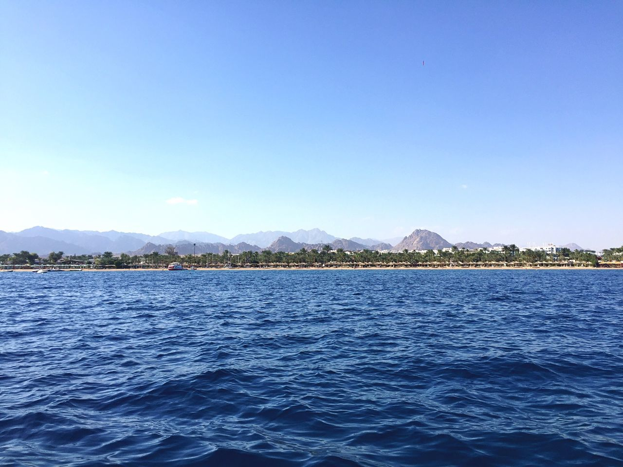 blue, tranquility, beauty in nature, nature, tranquil scene, mountain, water, scenics, no people, lake, waterfront, outdoors, clear sky, day, view into land, sky