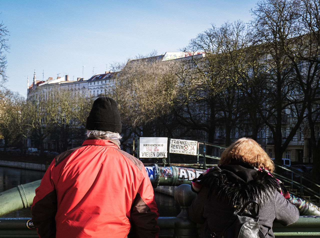Admiralbrücke Adult Berlin Tourism Blue Bridge City Couple Day Gap Kreuzberg Longing For Spring Old Couple Outdoors People Real People Rear View River Separated Separation Sky Tree Viewing Winter