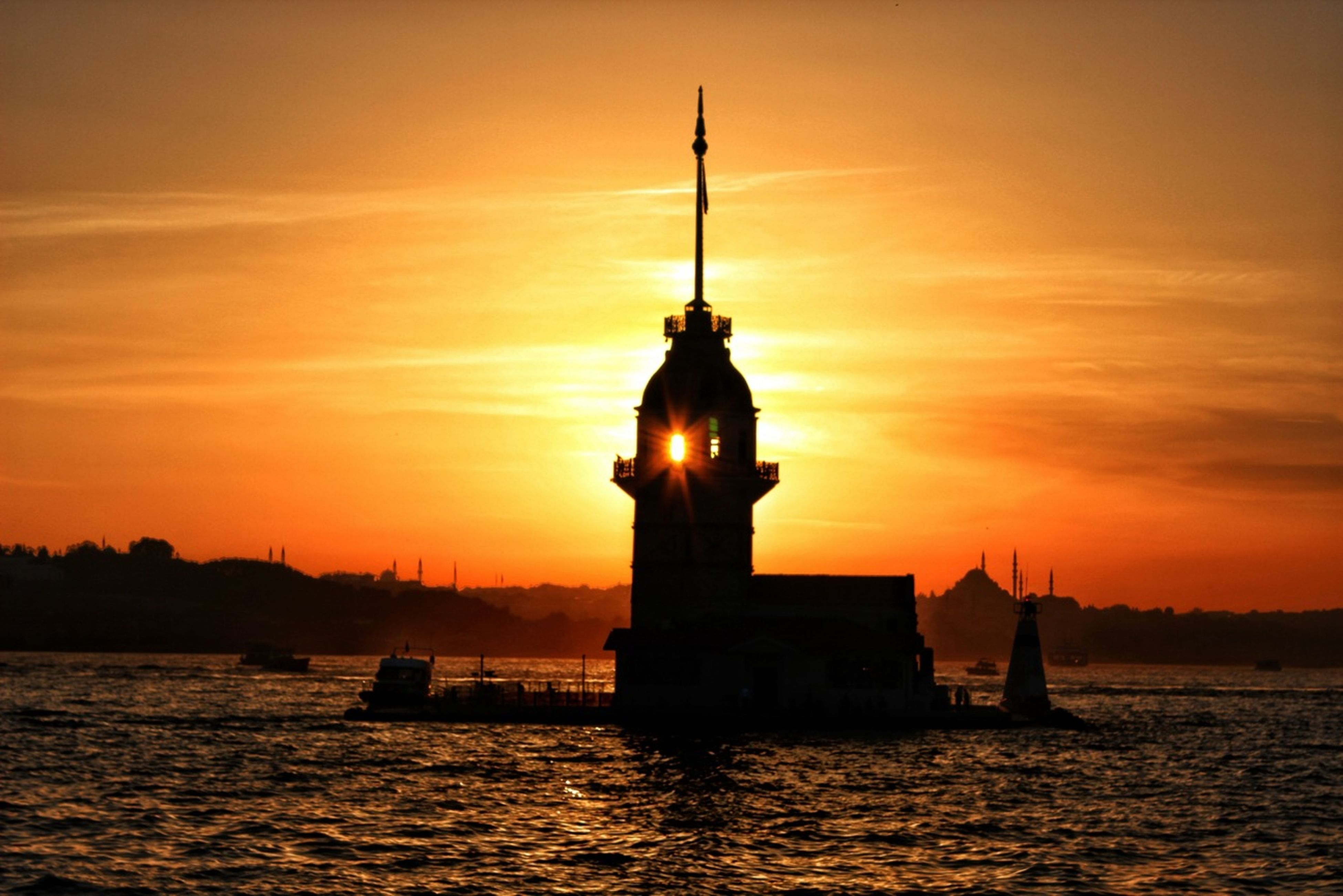 sunset, silhouette, water, orange color, waterfront, architecture, built structure, sea, sky, building exterior, sun, scenics, rippled, beauty in nature, lighthouse, nature, tranquility, tranquil scene, idyllic, cloud - sky