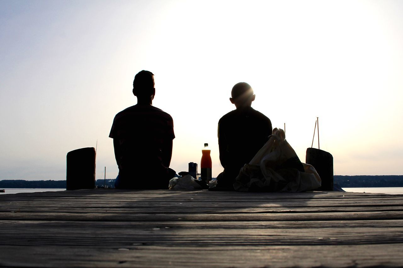 men, sea, real people, two people, sitting, silhouette, water, clear sky, outdoors, nature, women, sunset, togetherness, sky, day, beauty in nature, people
