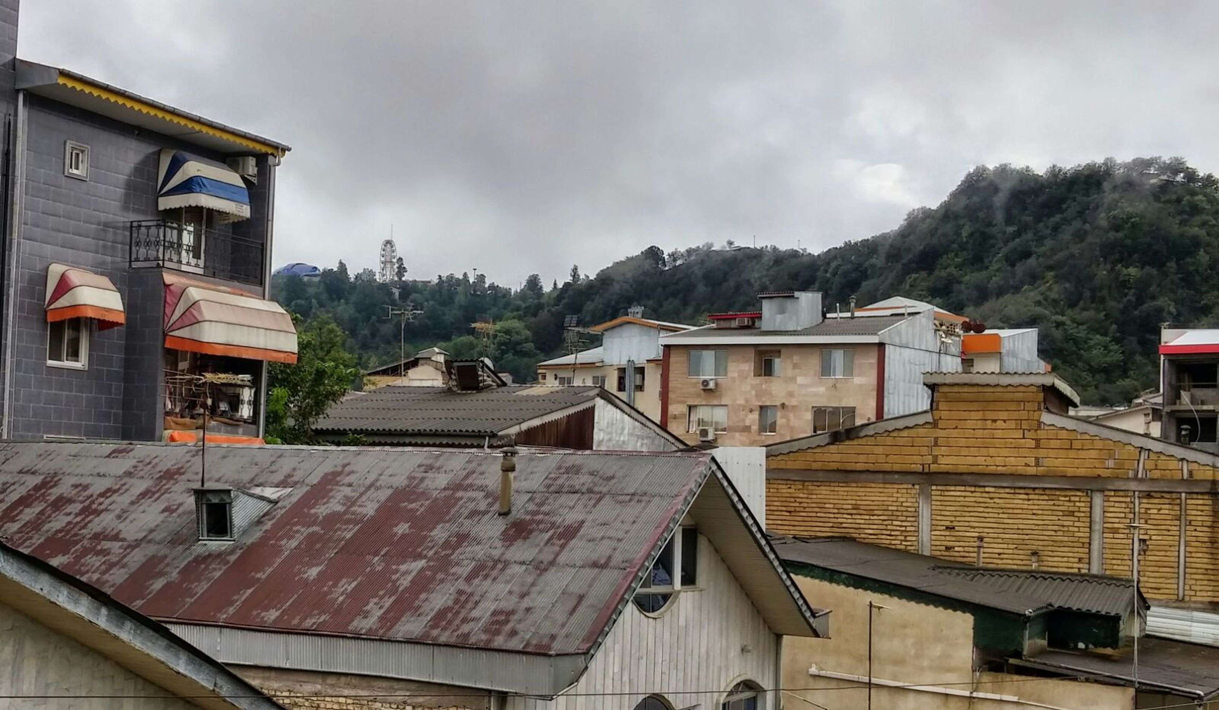architecture, building exterior, built structure, house, sky, mountain, residential structure, roof, residential building, cloud - sky, town, tree, cloudy, cloud, day, outdoors, railing, residential district, no people, building