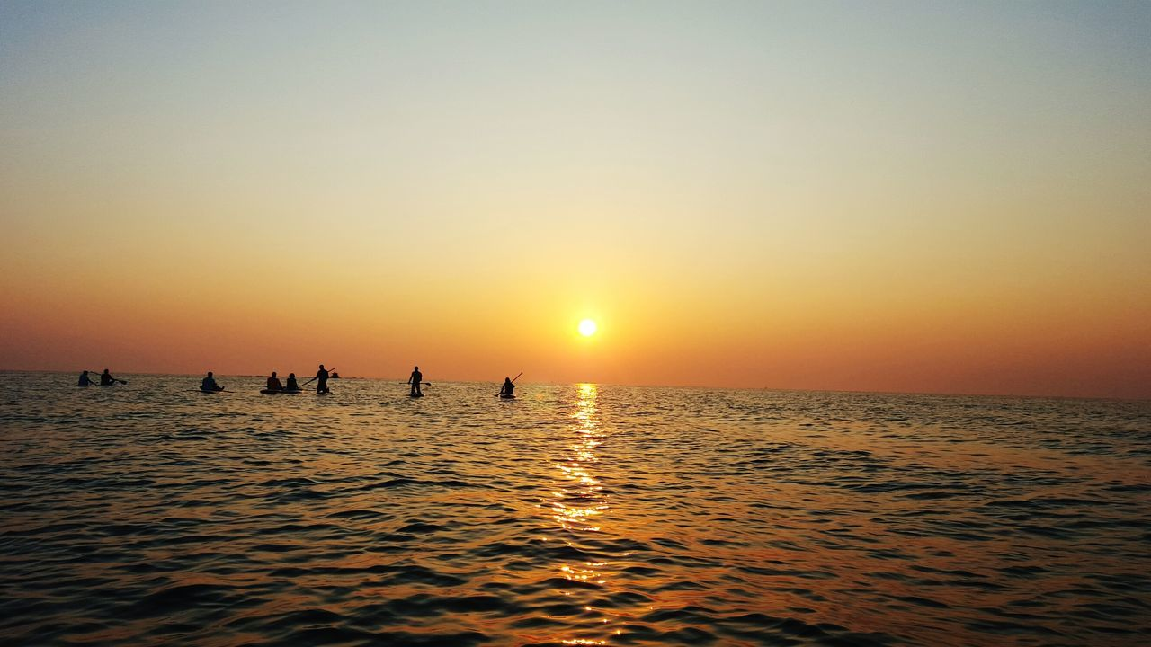 sunset, sea, water, beauty in nature, scenics, nature, silhouette, tranquil scene, sun, horizon over water, waterfront, tranquility, outdoors, sky, real people, clear sky, paddleboarding, day