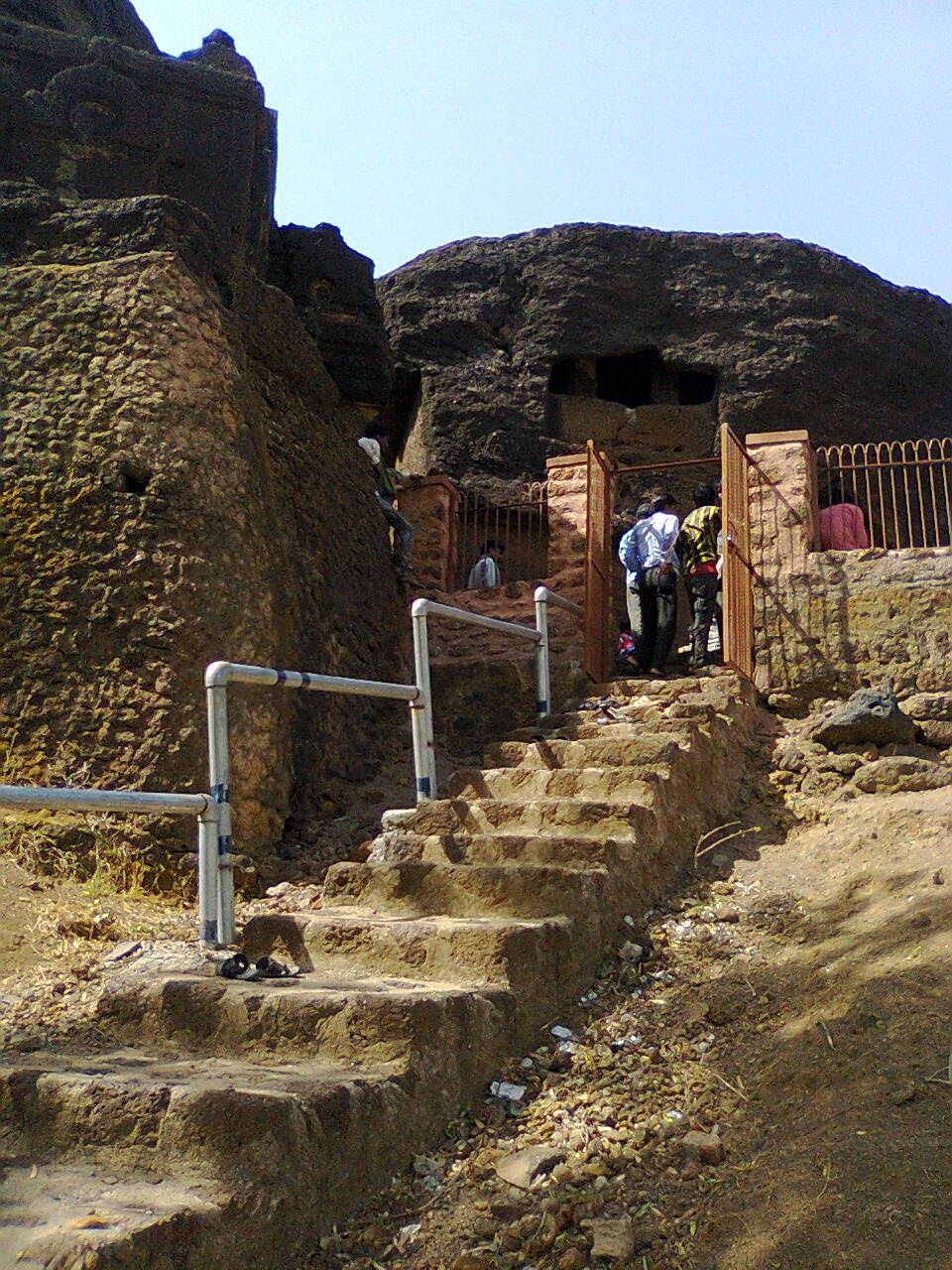 mountain, architecture, old ruin, built structure, real people, ancient, clear sky, history, ancient civilization, rock - object, day, outdoors, steps and staircases, nature, lifestyles, sunlight, building exterior, sky, travel destinations, landscape, men, standing, large group of people, people