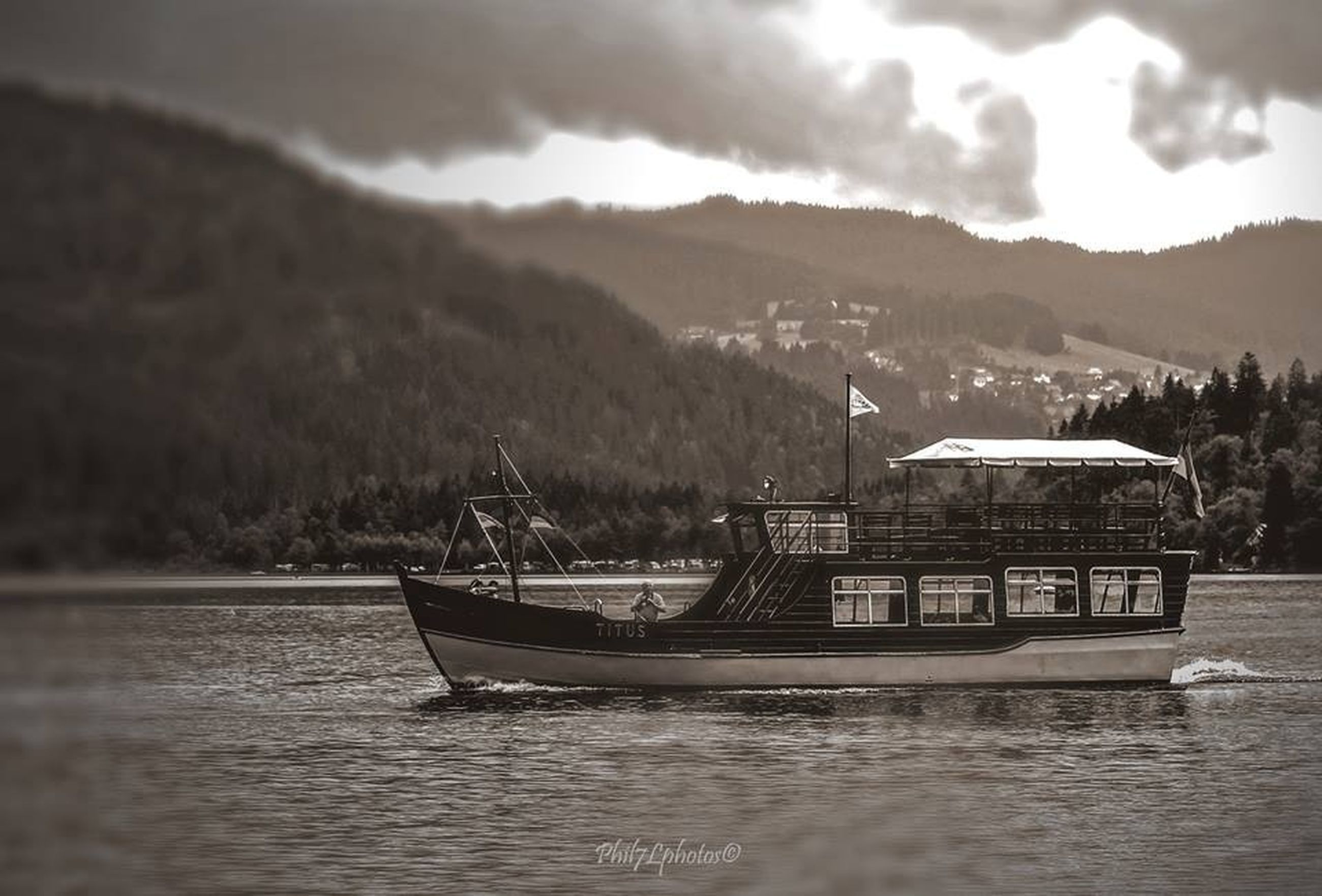 mountain, water, nautical vessel, transportation, waterfront, sky, mode of transport, boat, river, cloud - sky, lake, built structure, mountain range, building exterior, cloudy, architecture, moored, nature, tranquil scene, scenics