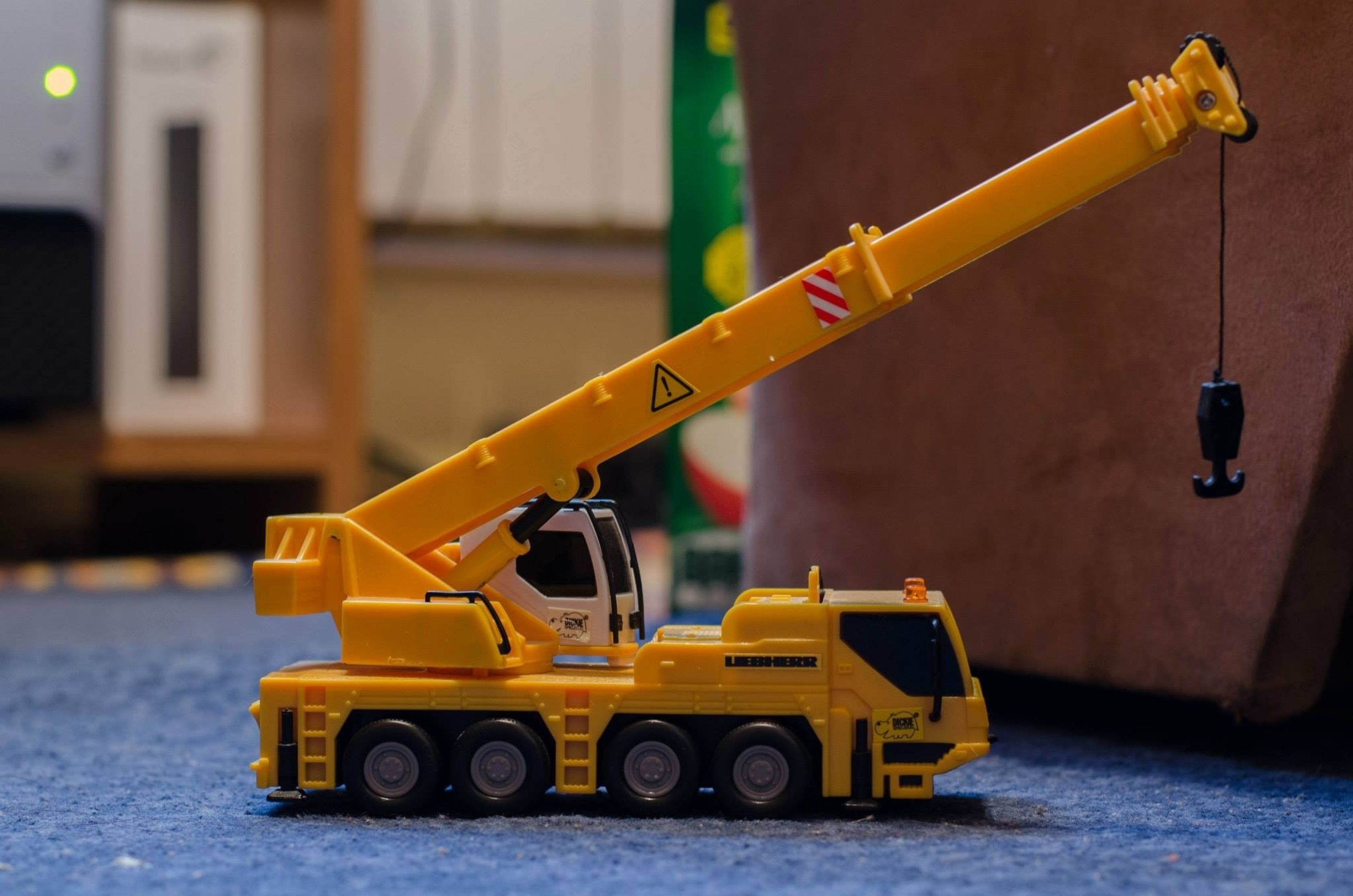 yellow, transportation, mode of transport, land vehicle, street, focus on foreground, built structure, close-up, outdoors, safety, toy, building exterior, no people, day, protection, car, architecture, metal, stationary, childhood