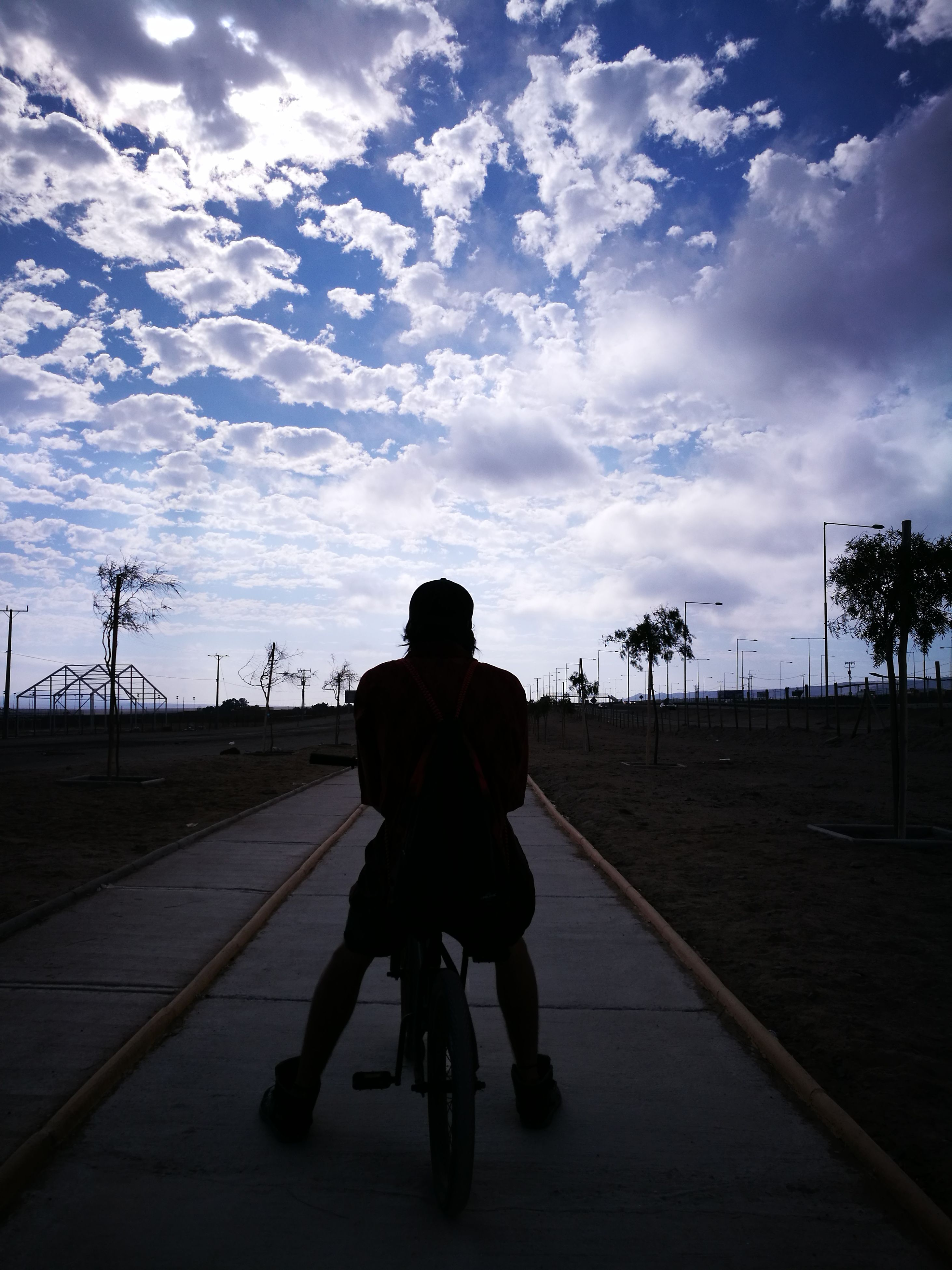 bicycle, transportation, riding, cycling, rear view, one person, cloud - sky, sky, real people, men, road, mode of transport, land vehicle, full length, outdoors, lifestyles, day, bmx cycling, one man only, nature, biker, adult, people