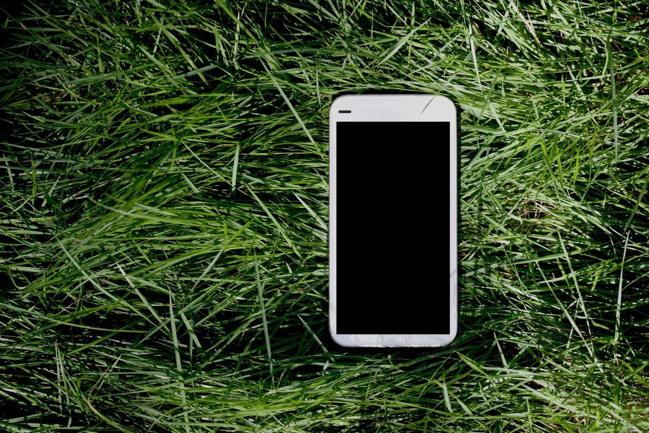 White smart phone on green grass background Smart Phones  IPhone Smartphone Grass Technology Gadgets Gadget White Cellphone Tablet